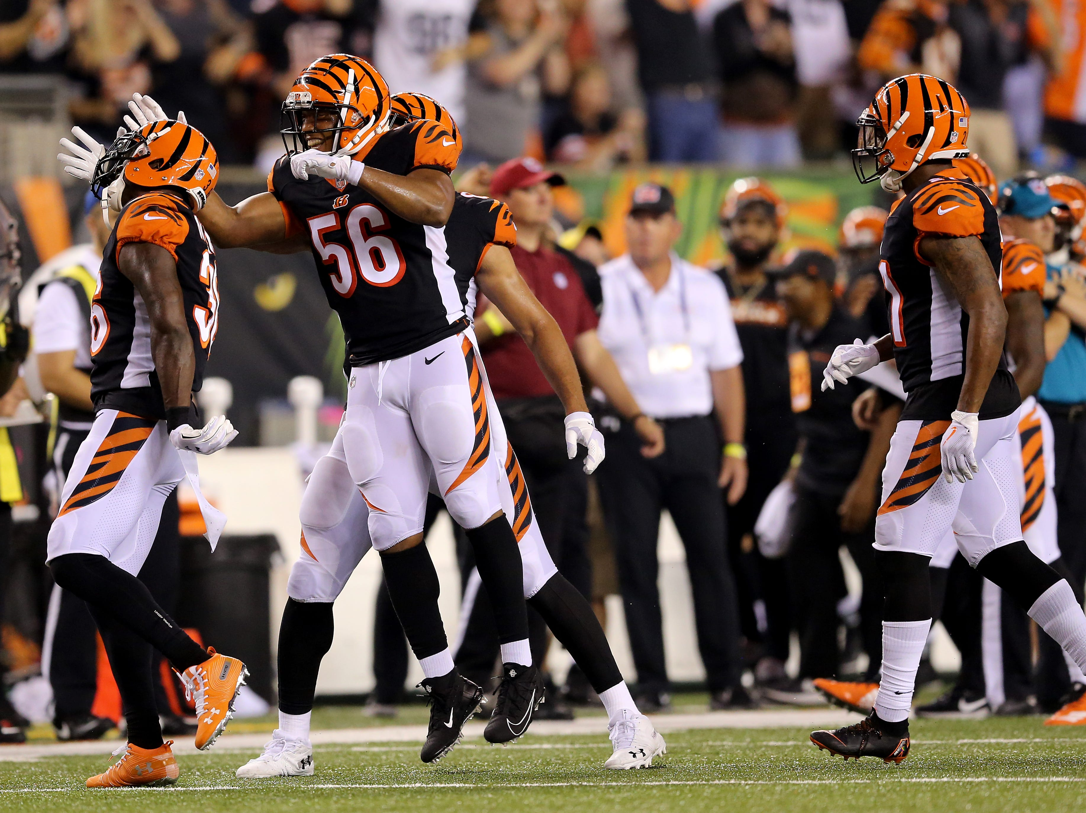 Cincinnati Bengals defensive back Shawn Williams (36), left, is congratulated by Cincinnati Bengals linebacker Hardy Nickerson (56), center, for his sack-fumble on Baltimore Ravens quarterback Joe Flacco (5) in the fourth quarter during the Week 2 NFL football game between the Baltimore Ravens and the Cincinnati Bengals, Friday, Sept. 14, 2018, Paul Brown Stadium in Cincinnati. Cincinnati won 34-23.