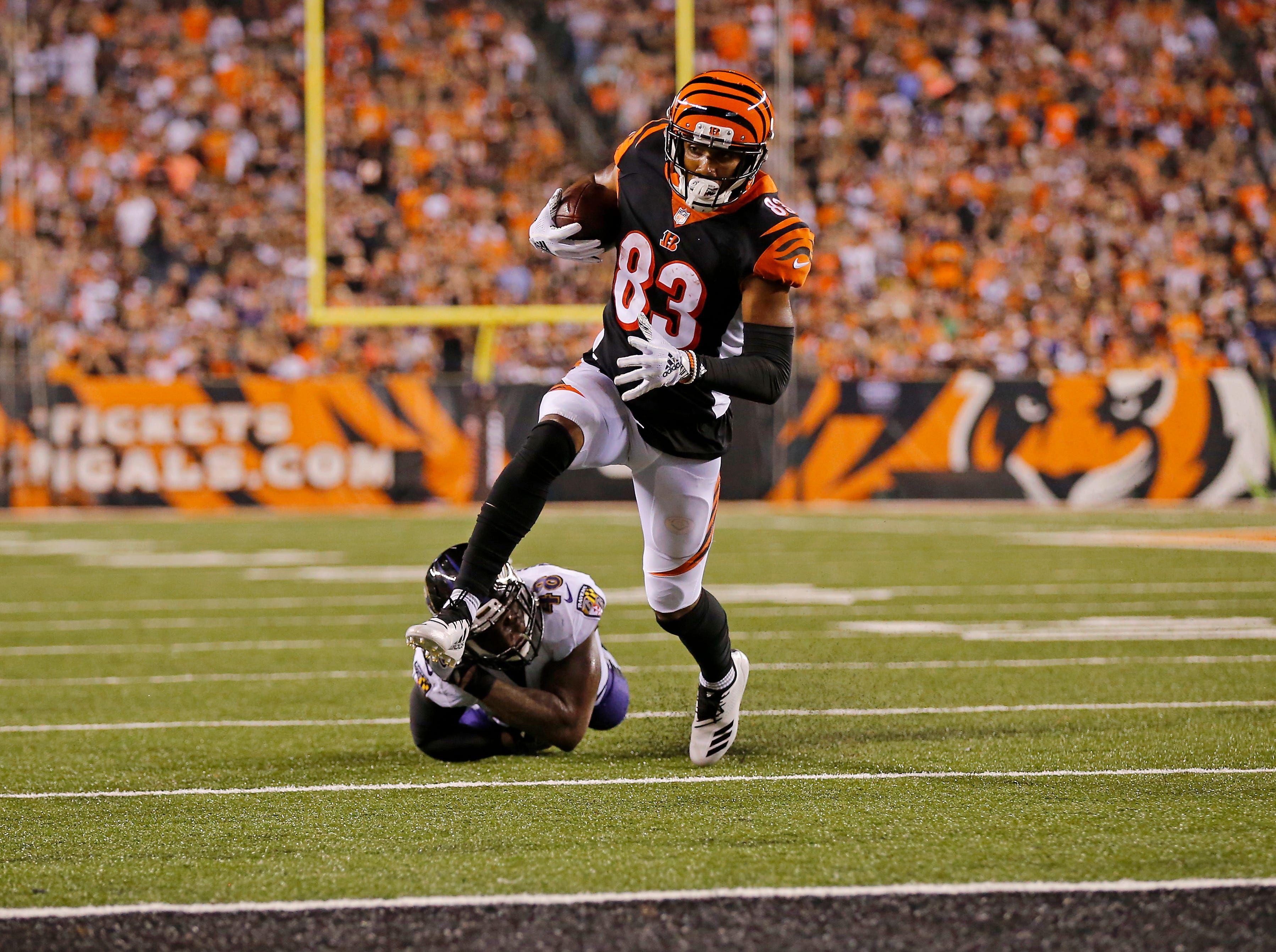 Cincinnati Bengals wide receiver Tyler Boyd (83) breaks a tackle from Baltimore Ravens linebacker Patrick Onwuasor (48) on his way to a touchdown in the second quarter of the NFL Week 2 game between the Cincinnati Bengals and the Baltimore Ravens at Paul Brown Stadium in downtown Cincinnati on Thursday, Sept. 13, 2018. The Bengals led 28-14 at halftime.