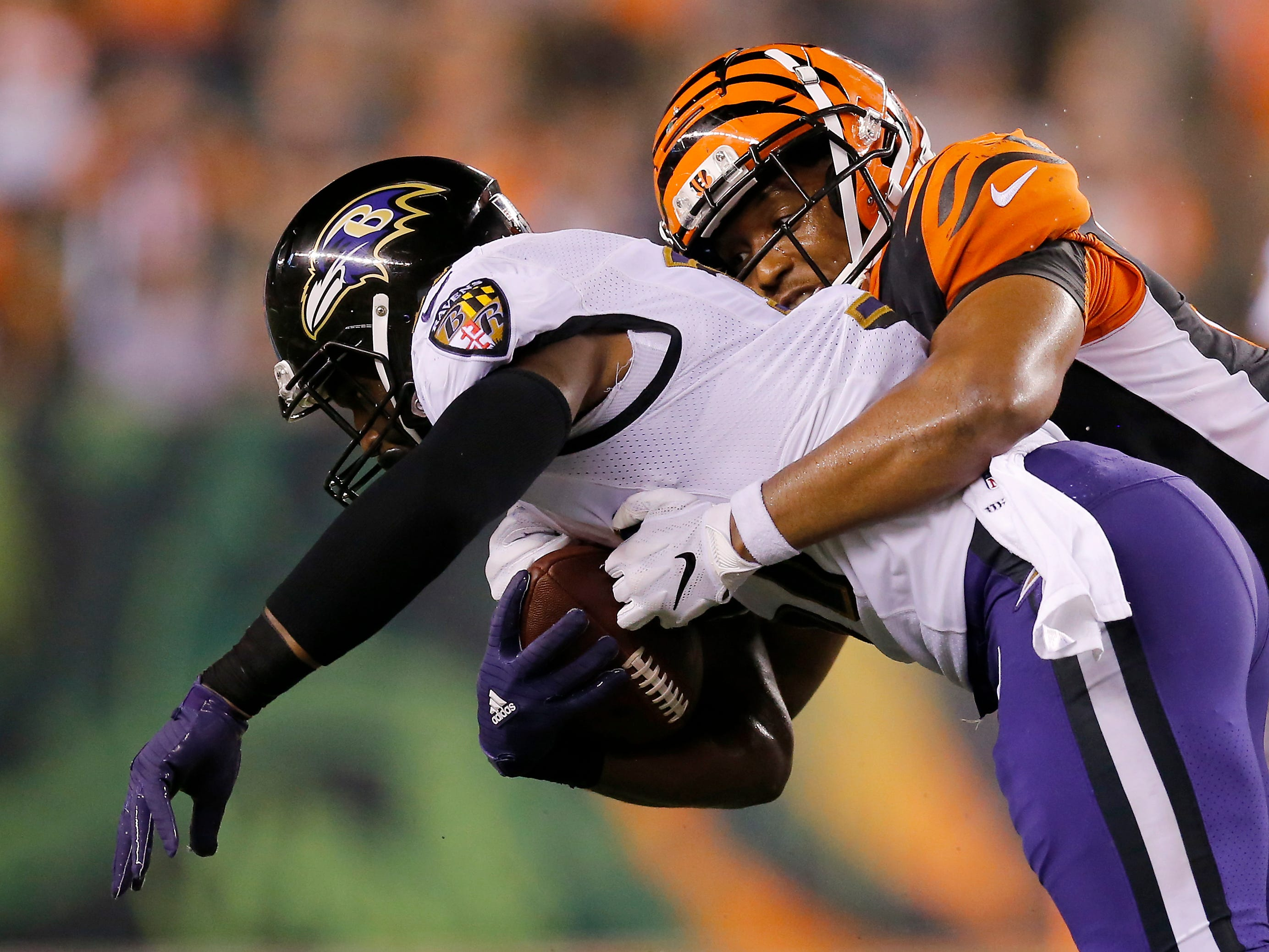 Baltimore Ravens running back Javorius Allen (37) is brought down Cincinnati Bengals linebacker Hardy Nickerson (56) in the fourth quarter of the NFL Week 2 game between the Cincinnati Bengals and the Baltimore Ravens at Paul Brown Stadium in downtown Cincinnati on Thursday, Sept. 13, 2018. The Bengals improved to 2-0 on the season with a 34-23 win over the Ravens.