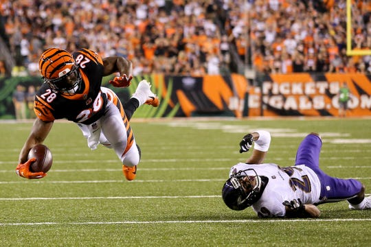 Cincinnati Bengals running back Joe Mixon (28) is upended by Baltimore Ravens defensive back Brandon Carr (24) in the first quarter during the Week 2 NFL football game between the Baltimore Ravens and the Cincinnati Bengals, Thursday, Sept. 13, 2018, Paul Brown Stadium in Cincinnati.