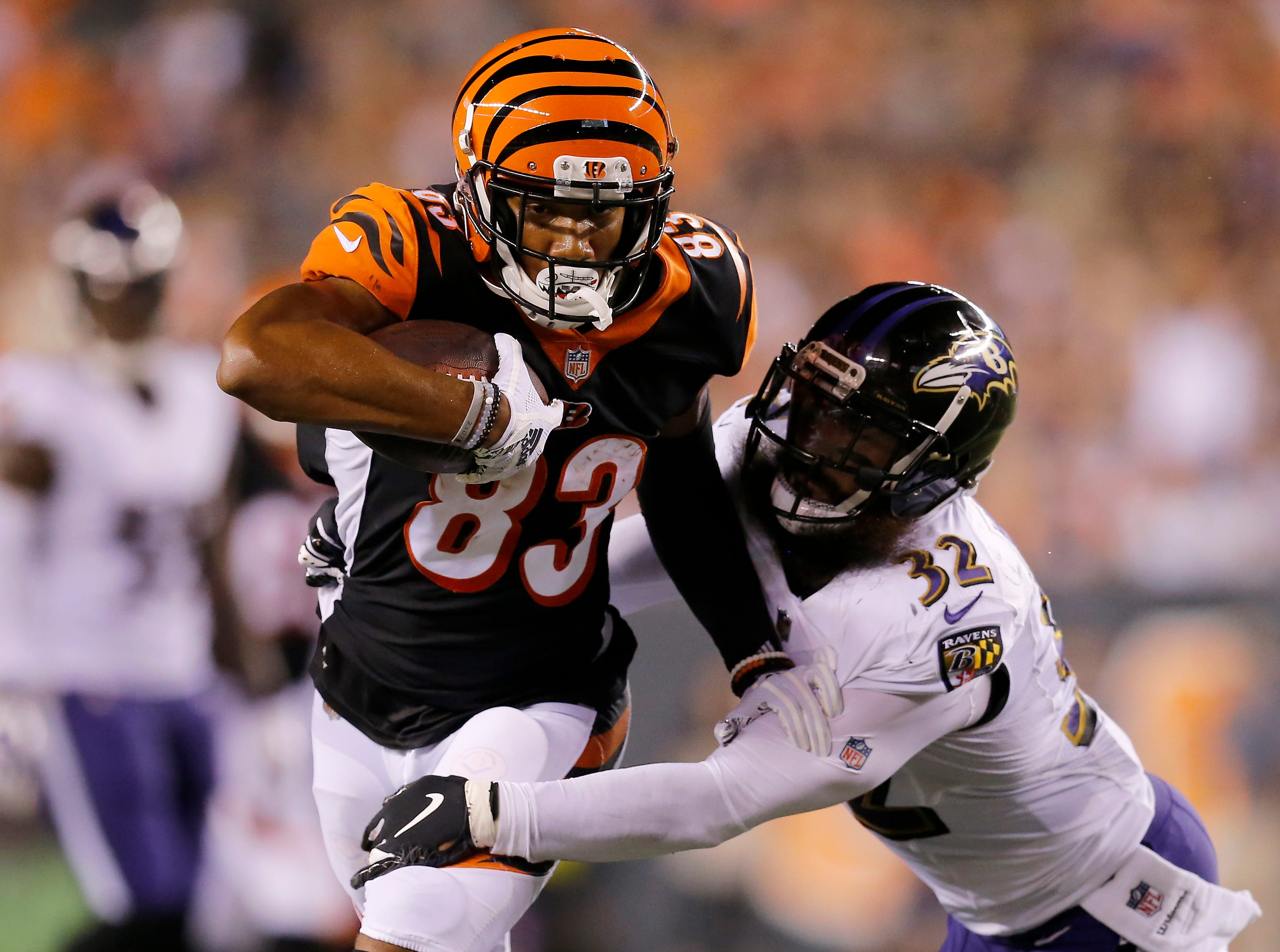 Cincinnati Bengals wide receiver Tyler Boyd (83) fights a tackle from Baltimore Ravens defensive back Eric Weddle (32) in the second quarter of the NFL Week 2 game between the Cincinnati Bengals and the Baltimore Ravens at Paul Brown Stadium in downtown Cincinnati on Thursday, Sept. 13, 2018. The Bengals led 28-14 at halftime.