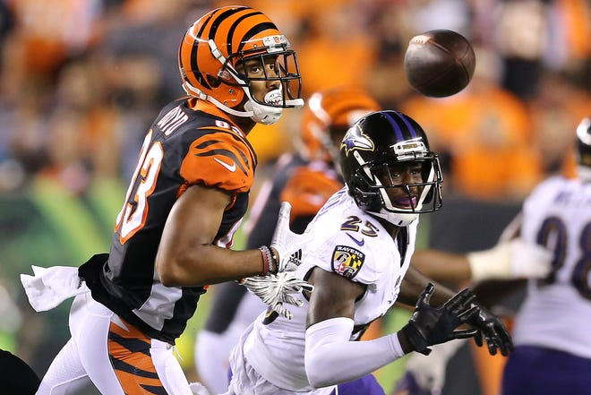 Cincinnati Bengals wide receiver Tyler Boyd (83) and Baltimore Ravens cornerback Tavon Young (25) eye a tipped ball in the fourth quarter during the Week 2 NFL football game between the Baltimore Ravens and the Cincinnati Bengals, Friday, Sept. 14, 2018, Paul Brown Stadium in Cincinnati. Cincinnati won 34-23.