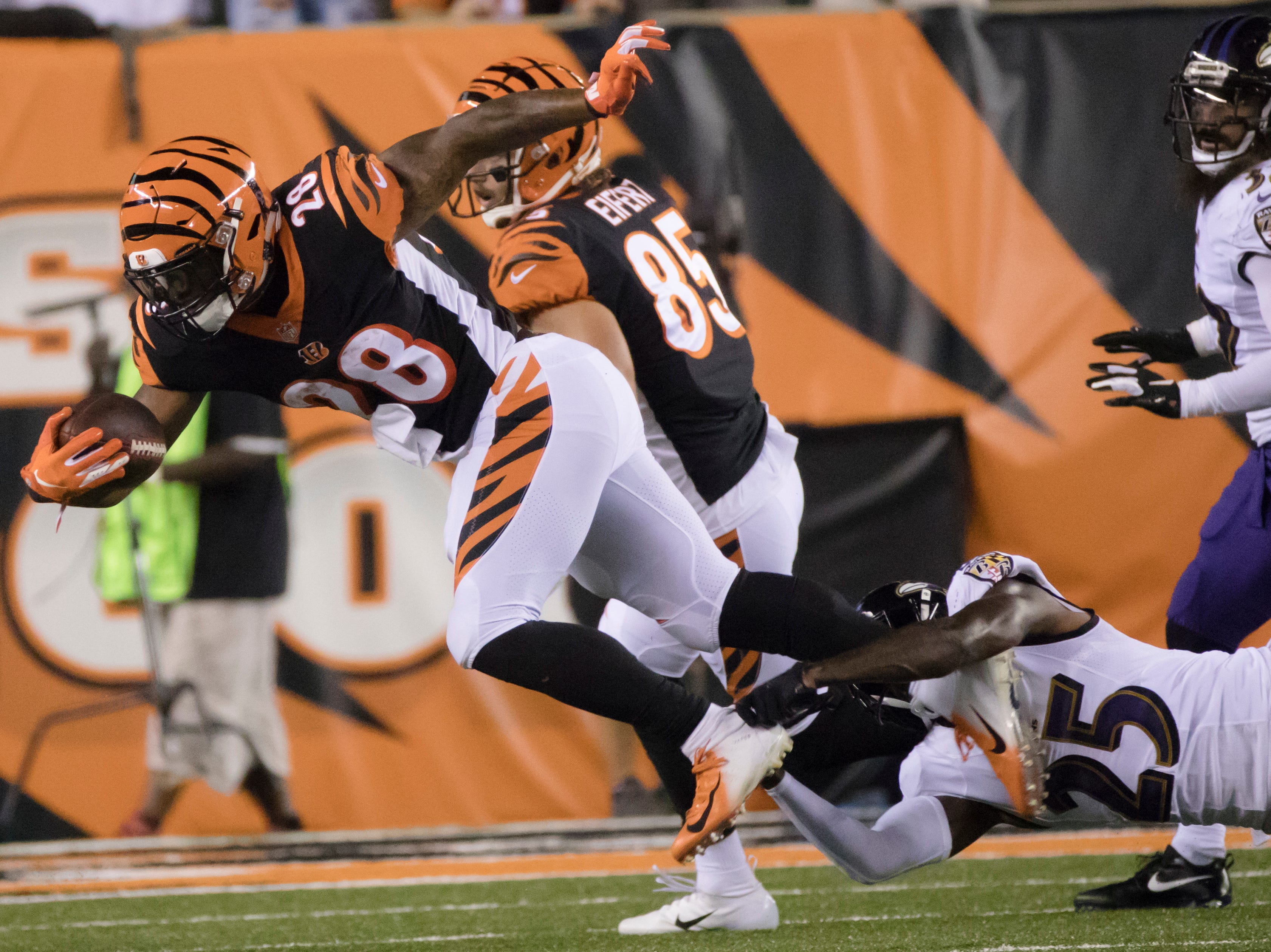 Baltimore Ravens cornerback Tavon Young (25) tackles Cincinnati Bengals running back Joe Mixon (28) during the Week 2 NFL game between the Cincinnati Bengals and the Baltimore Ravens, Thursday, Sept. 13, 2018, at Paul Brown Stadium in Cincinnati.