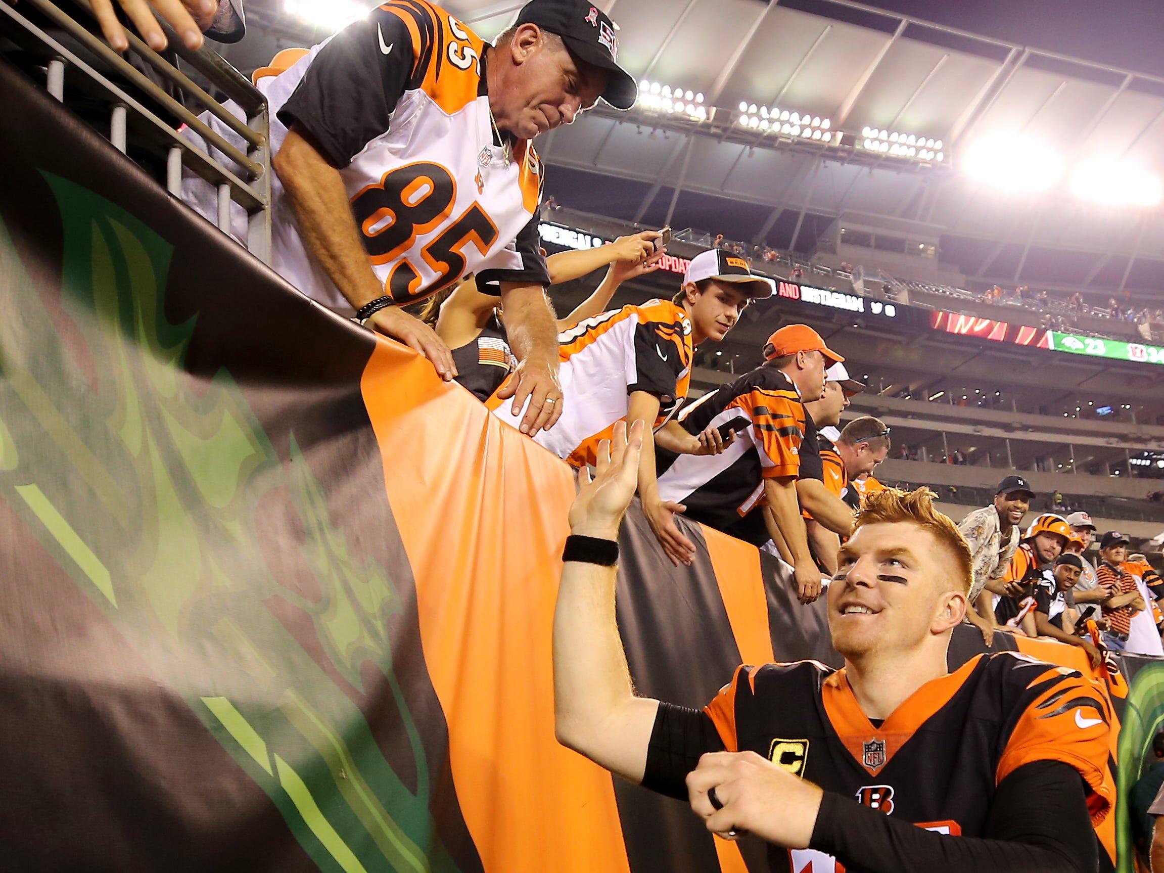 Cincinnati Bengals quarterback Andy Dalton (14) high fives fans after the Week 2 NFL football game between the Baltimore Ravens and the Cincinnati Bengals, Friday, Sept. 14, 2018, Paul Brown Stadium in Cincinnati. Cincinnati won 34-23.