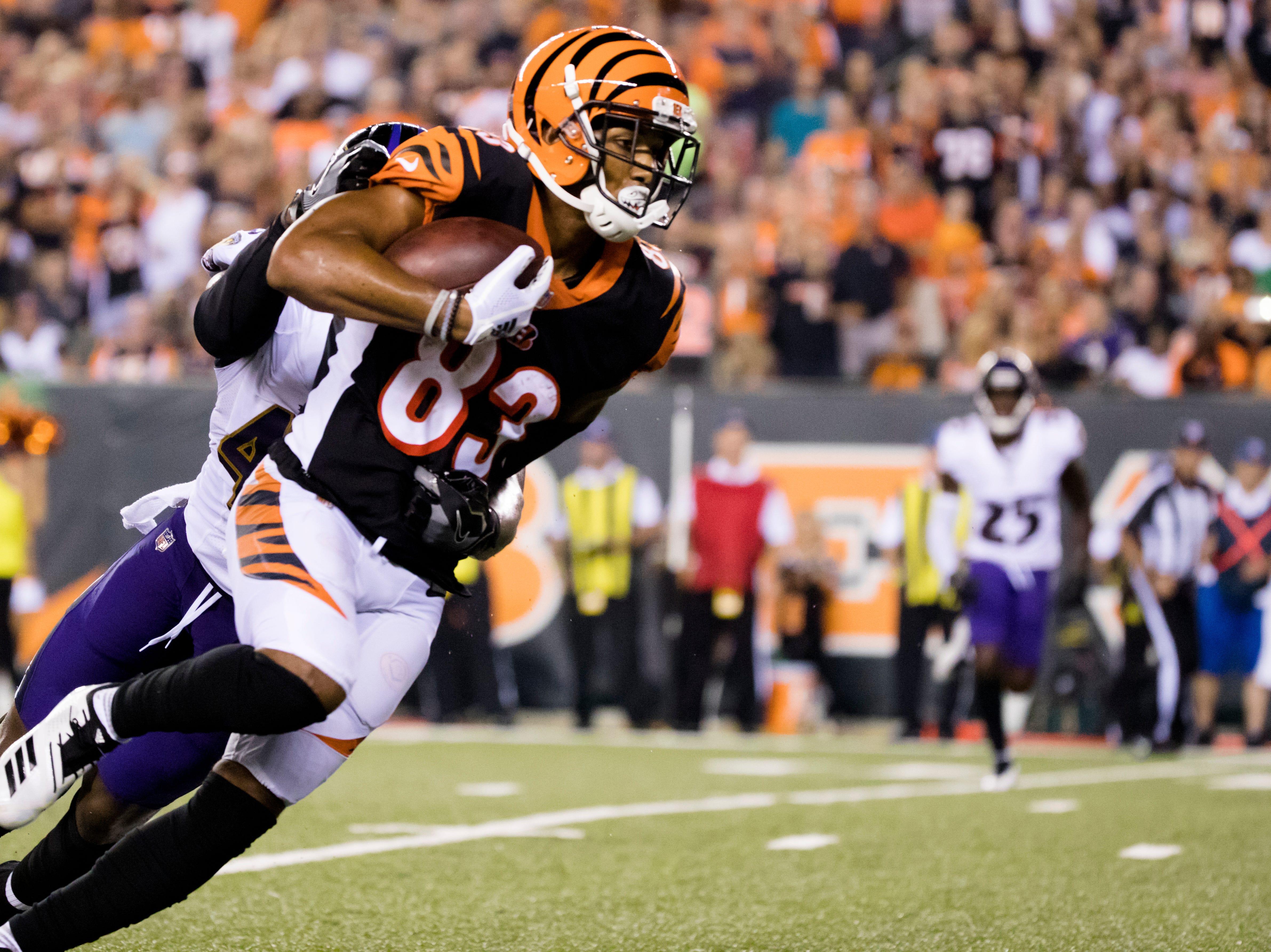 Cincinnati Bengals wide receiver Tyler Boyd (83) slips a tackle attempt by Baltimore Ravens linebacker Patrick Onwuasor (48) before scoring a touchdown during the Week 2 NFL game between the Cincinnati Bengals and the Baltimore Ravens, Thursday, Sept. 13, 2018, at Paul Brown Stadium in Cincinnati.