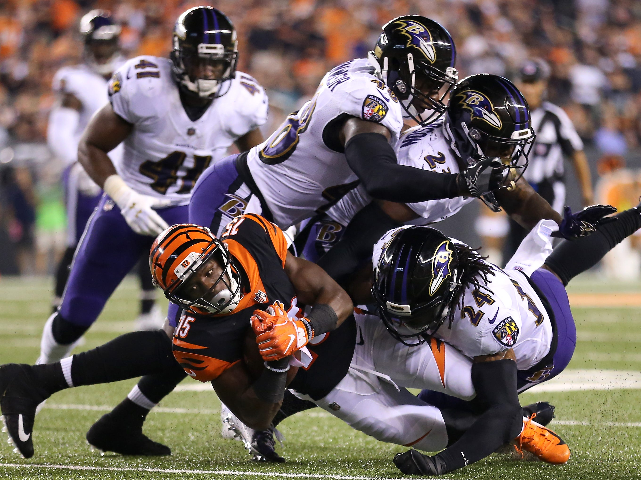 Cincinnati Bengals wide receiver John Ross (15) leans forward for extra yards as Baltimore Ravens defensive back Brandon Carr (24) makes the tackle in the fourth quarter during the Week 2 NFL football game between the Baltimore Ravens and the Cincinnati Bengals, Friday, Sept. 14, 2018, Paul Brown Stadium in Cincinnati. Cincinnati won 34-23.
