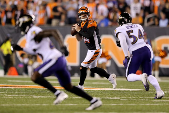 Cincinnati Bengals quarterback Andy Dalton (14) rolls out of the pocket in the first quarter during the Week 2 NFL football game between the Baltimore Ravens and the Cincinnati Bengals, Thursday, Sept. 13, 2018, Paul Brown Stadium in Cincinnati.