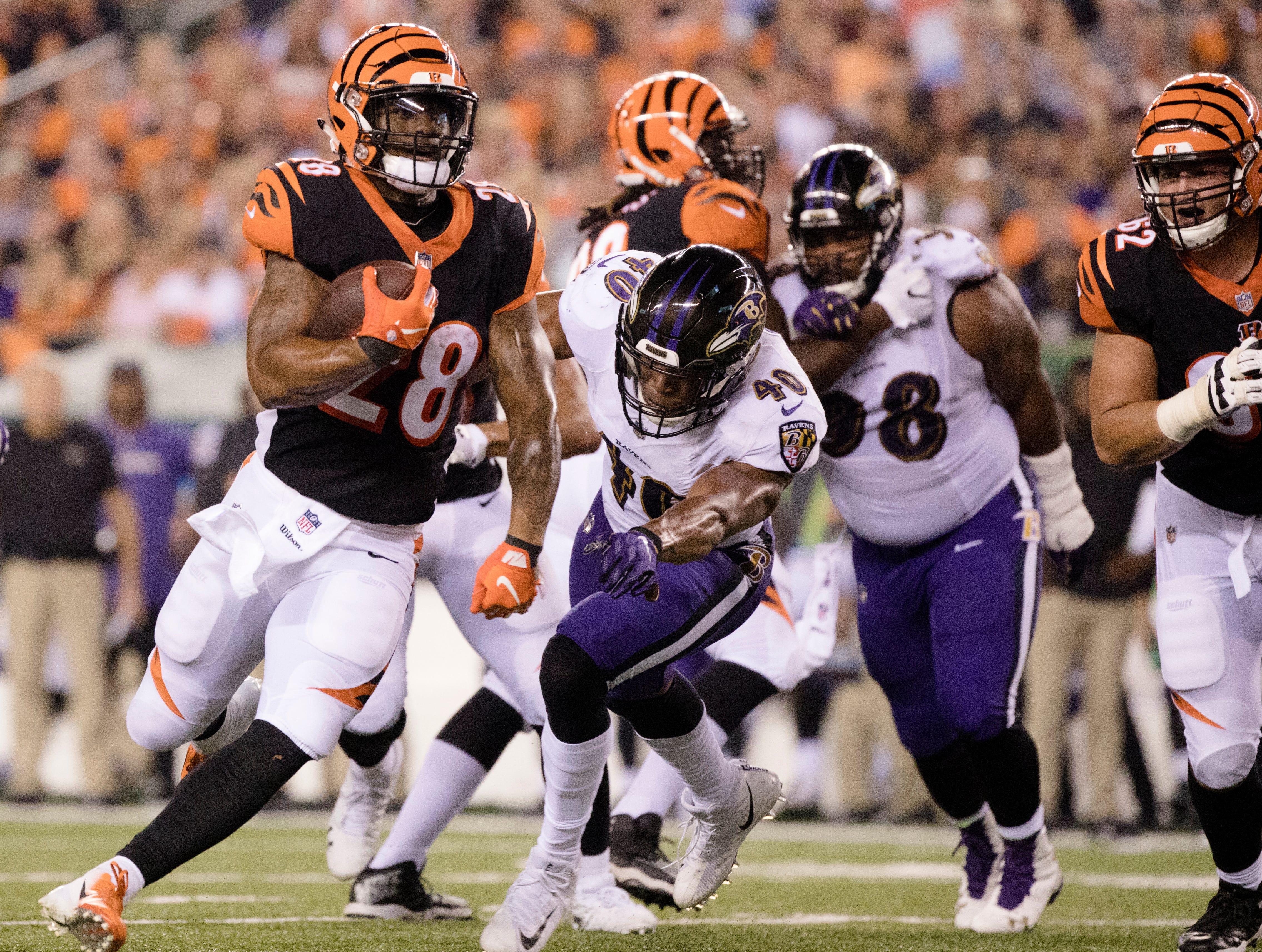 Cincinnati Bengals running back Joe Mixon (28) runs past Baltimore Ravens linebacker Kenny Young (40) during the Week 2 NFL game between the Cincinnati Bengals and the Baltimore Ravens, Thursday, Sept. 13, 2018, at Paul Brown Stadium in Cincinnati.