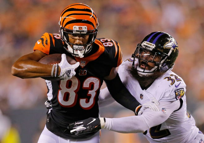 Cincinnati Bengals wide receiver Tyler Boyd (83) fights off a tackle from Baltimore Ravens defensive back Eric Weddle (32) in the third quarter of the NFL Week 2 game between the Cincinnati Bengals and the Baltimore Ravens at Paul Brown Stadium in downtown Cincinnati on Thursday, Sept. 13, 2018. The Bengals led 28-14 at halftime.
