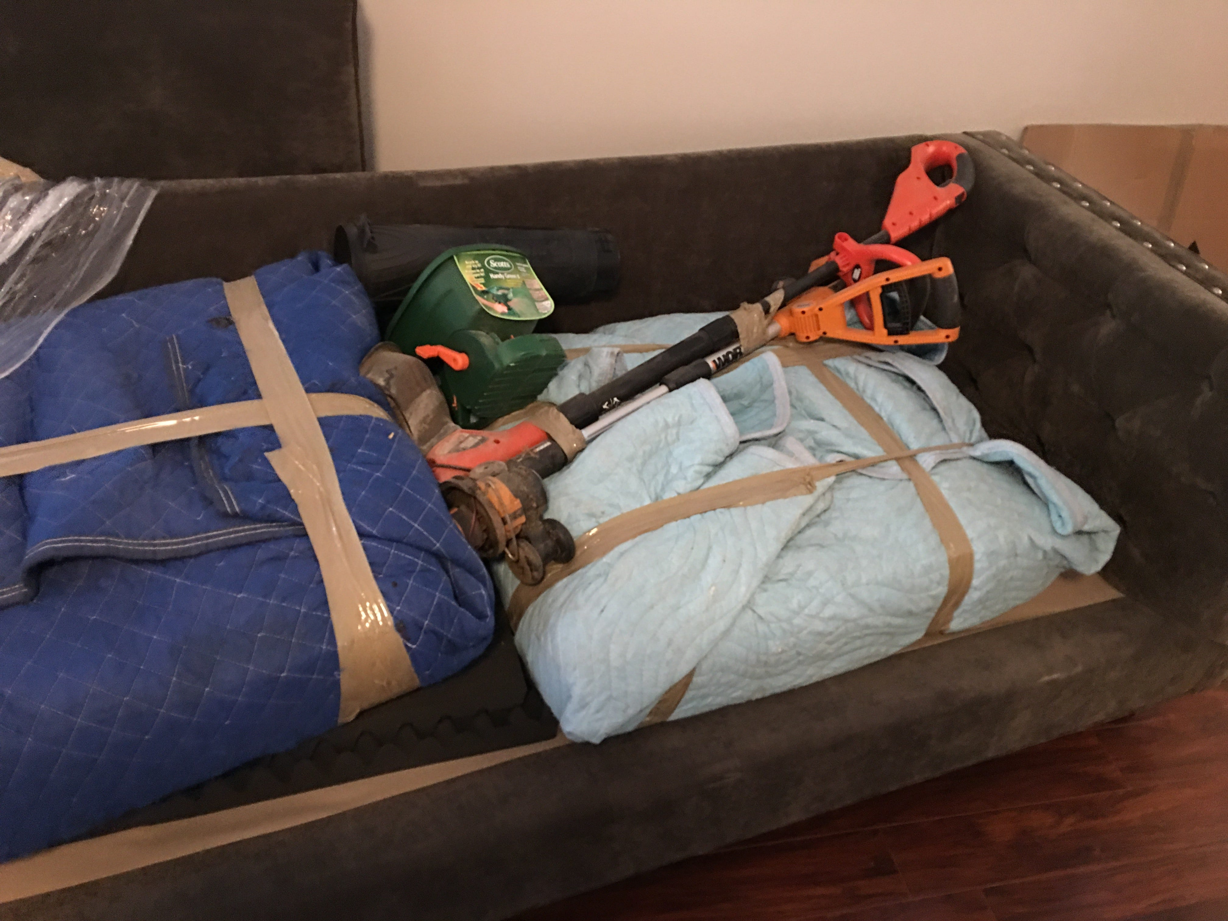 A dirtied couch stacked with lawn equipment from the O'Neill family move from Fort Campbell, KY, this summer by A2B Moving and Delivery.