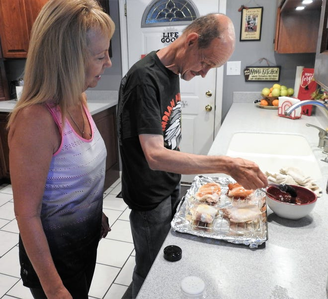David Hahn bastes chicken with sweet and sour sauce while Deana Cushman observes. Cushman is a direct support professional who works with Hahn. Cooking is one of his favorite hobbies.