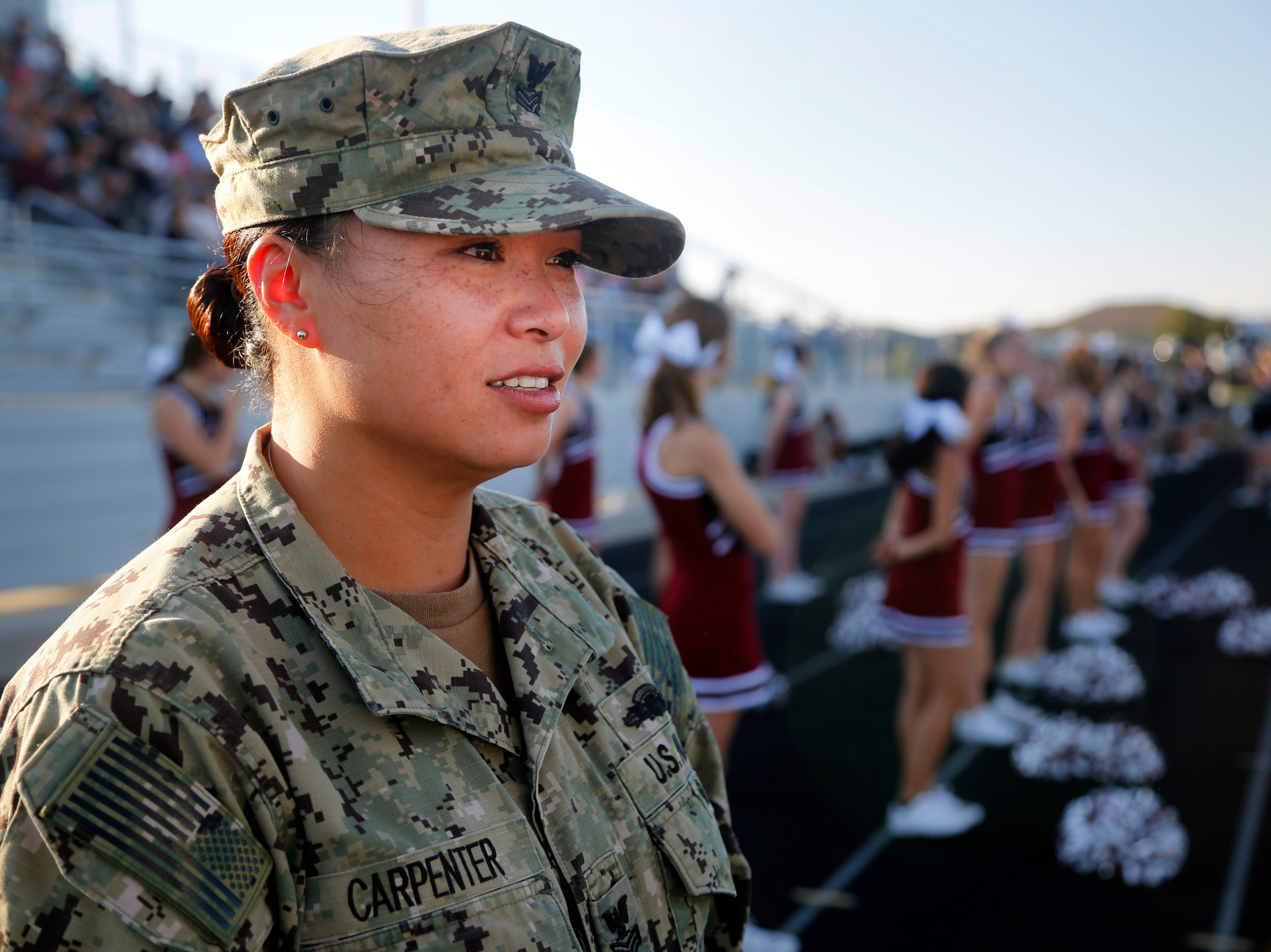 Navy Gunner Mate 1st Class Expeditionary Warfare Specialist Diem Carpenter stands on the sidelines after returning home after 10 months to surprise her son Gabriel Arrendondo, a member of Ankeny Centennial's sophomore football team at his game Sept. 14, 2018.
