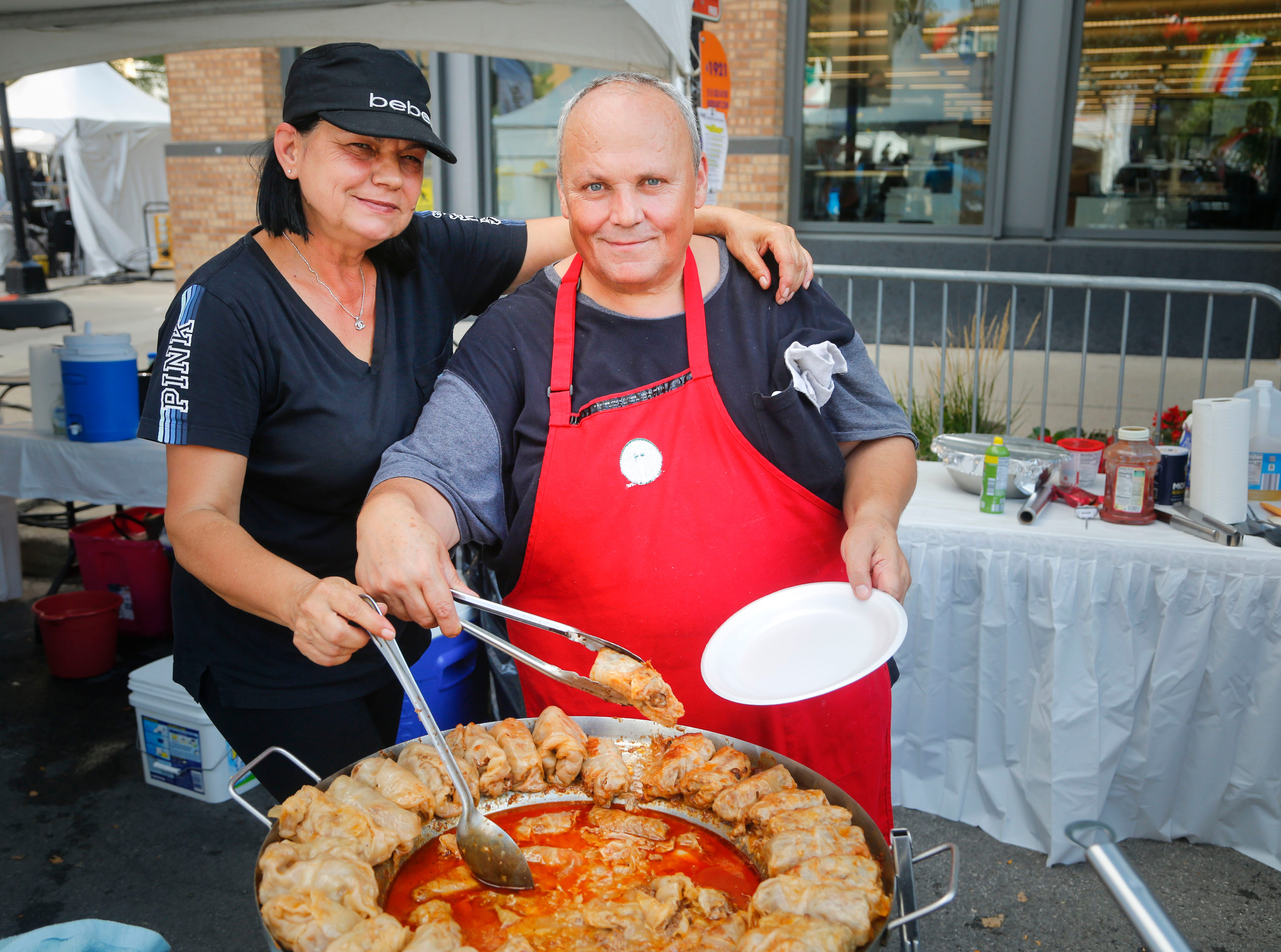 Rada and Joe Dzehvid load up a plate of food at the Papillon Bosnian Food booth at the World Food and Music Festival in Des Moines Sept. 14, 2018.