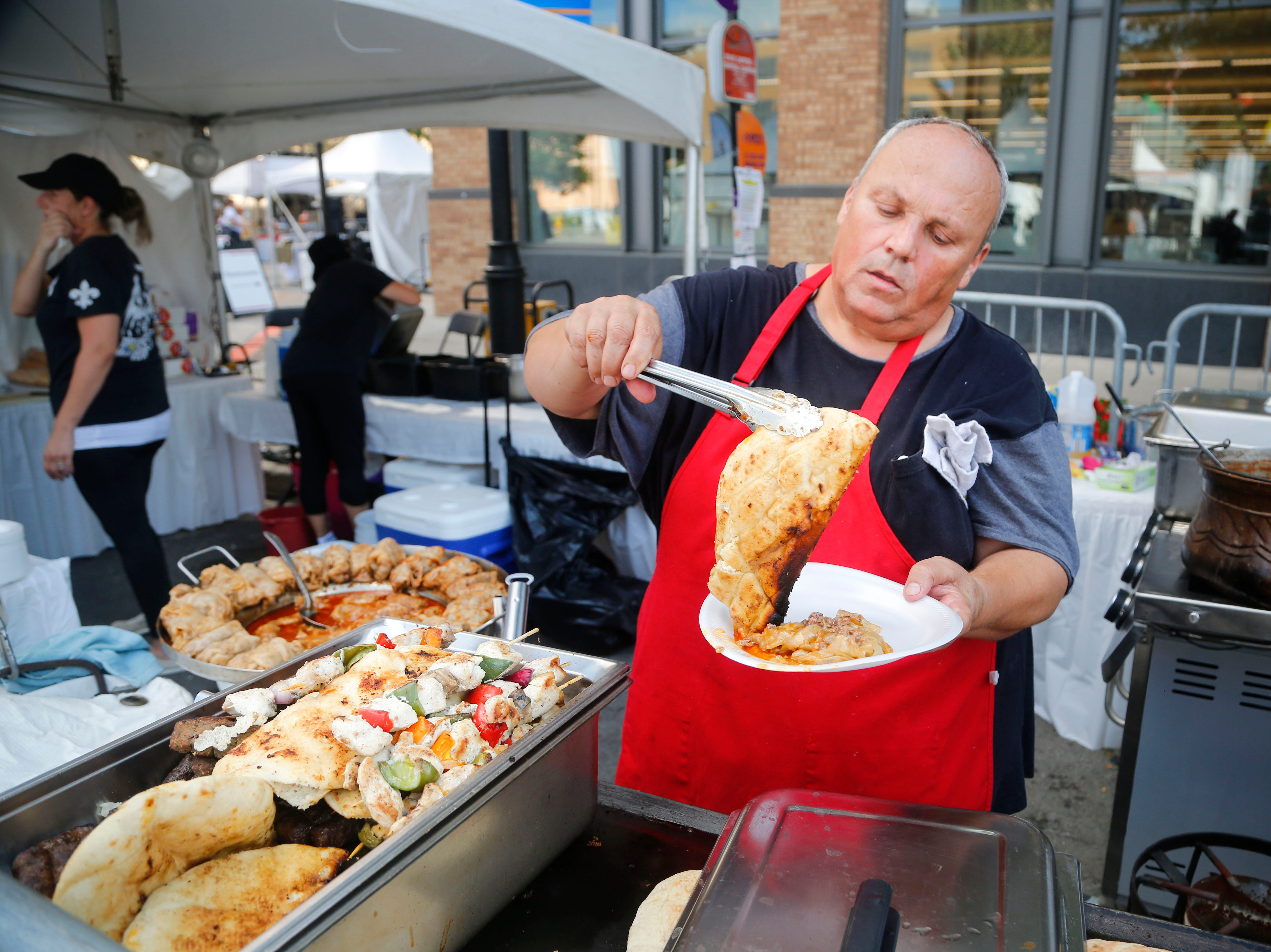 Joe Dzehvid loads up a plate of food at the Papillon Bosnian Food booth at the World Food and Music Festival in Des Moines Sept. 14, 2018.