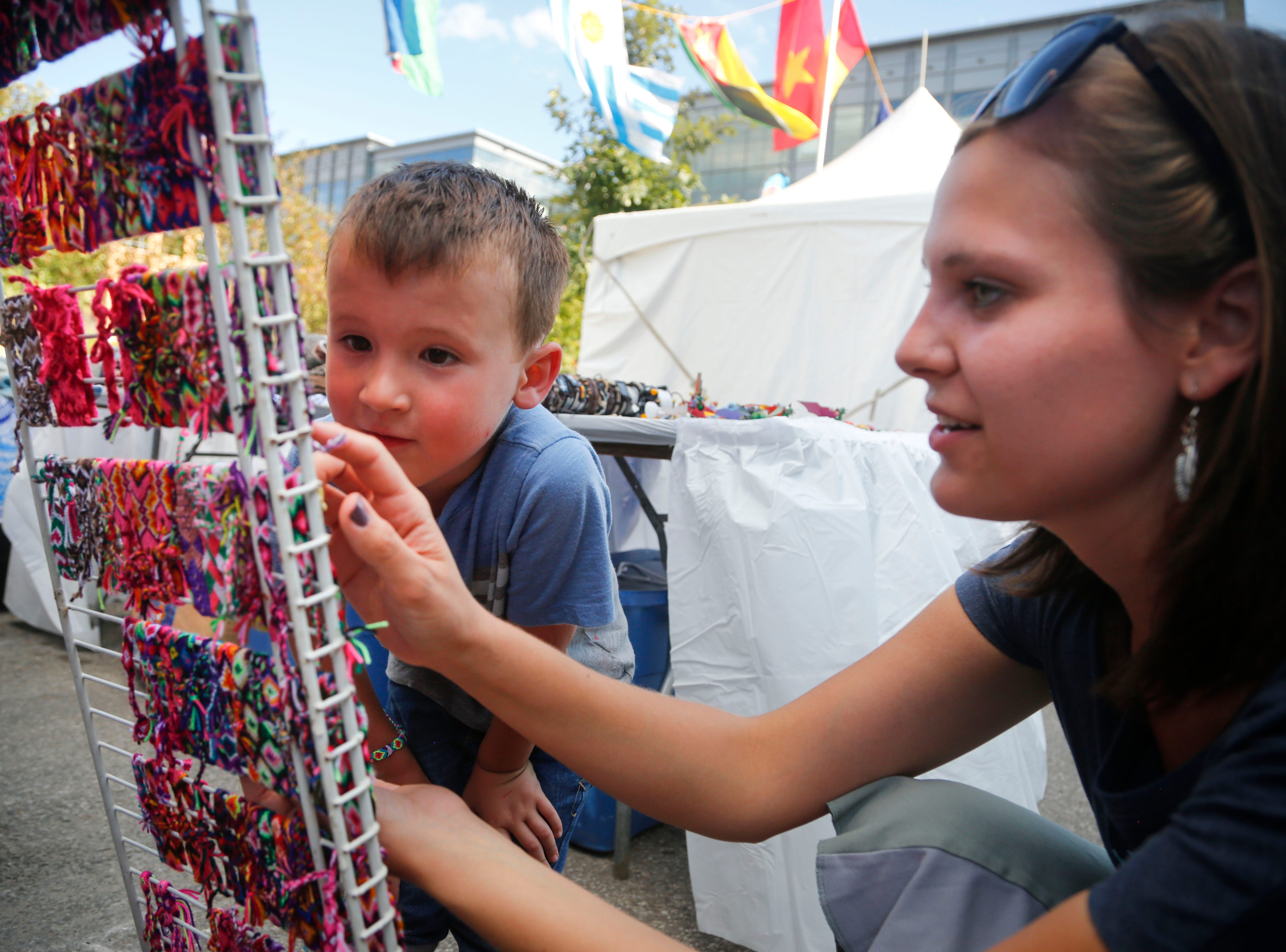 Isaac Byers, 5, and his mother laura check out bracelets from Terranova Fine Arts at the World Food and Music Festival in Des Moines Sept. 14, 2018.