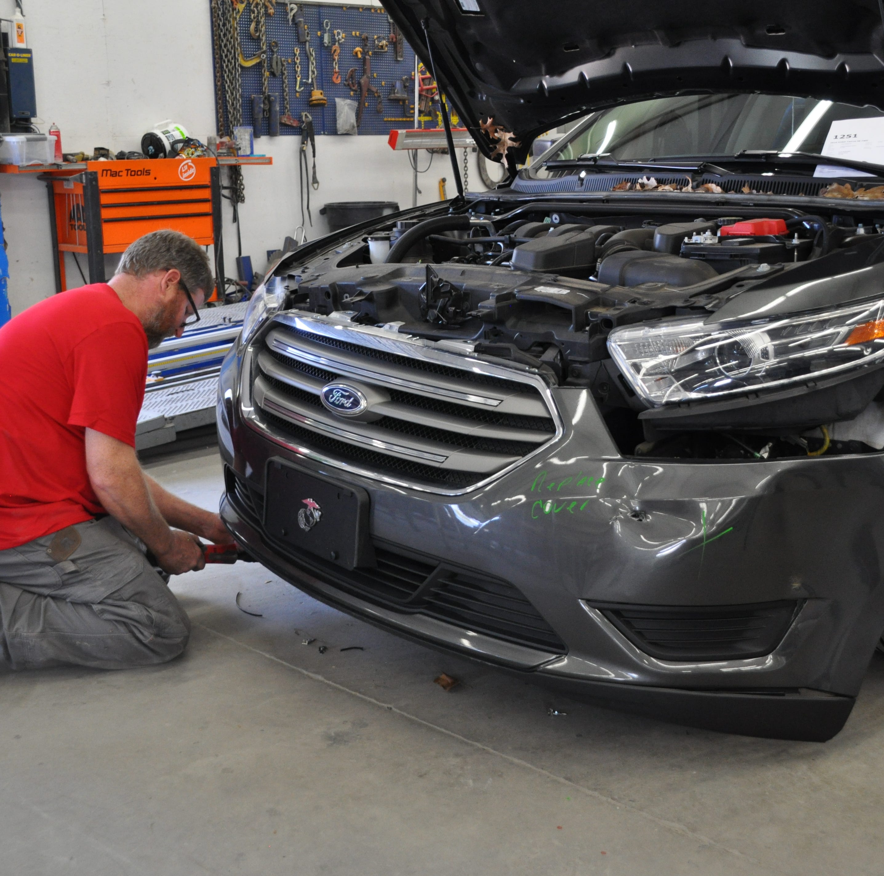 A repair technician removes a car's front bumper assembly, which houses numerous sensors to support safe driving technology, during a repair at Carstar Lexington Collision in Lexington, S.C.