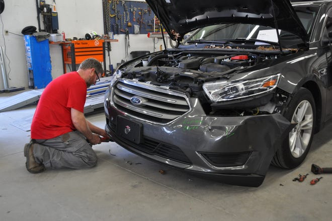 Repair technician Mark Johnstone removes a car's front bumper assembly, which houses numerous sensors to support safe driving technology, during a repair at Carstar Lexington Collision in Lexington, S.C., in February.