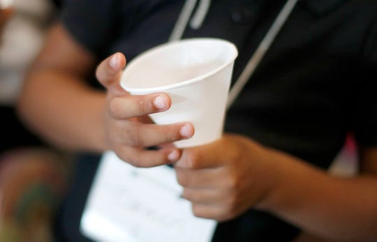 A student holds a cup for water dispensed from a cooler in the hallway at Gardner Elementary School in Detroit, Tuesday, Sept. 4, 2018. Some 50,000 Detroit public school students will start the 2018 school year by drinking water from coolers, not fountains, after the discovery of elevated levels of lead or copper.