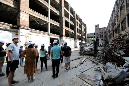 People look around at the scope of the buildings as a tour guide gives them historical information during the Pure Detroit tour, in partnership with Arte Express, of the Albert Kahn Associates designed Packard Automotive Plant in Detroit on Saturday, Aug. 12, 2018.