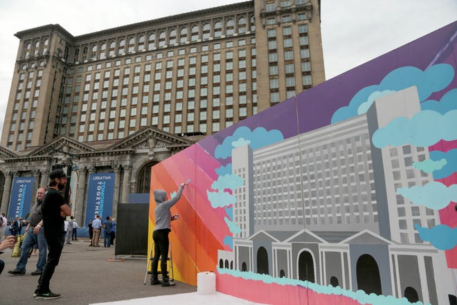 An artist works on a painting of the Michigan Central Station during the celebration of the Ford Motor Company buying the Michigan Central Station in Corktown, a Detroit neighborhood, on Tuesday, June 19, 2018.