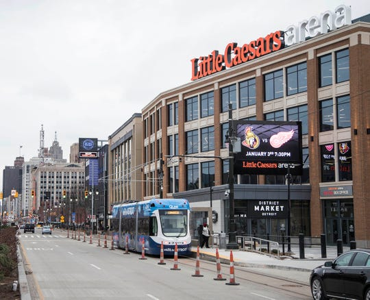 A QLine streetcar goes by the Little Caesars Arena in Detroit, Thursday, December 21, 2017.