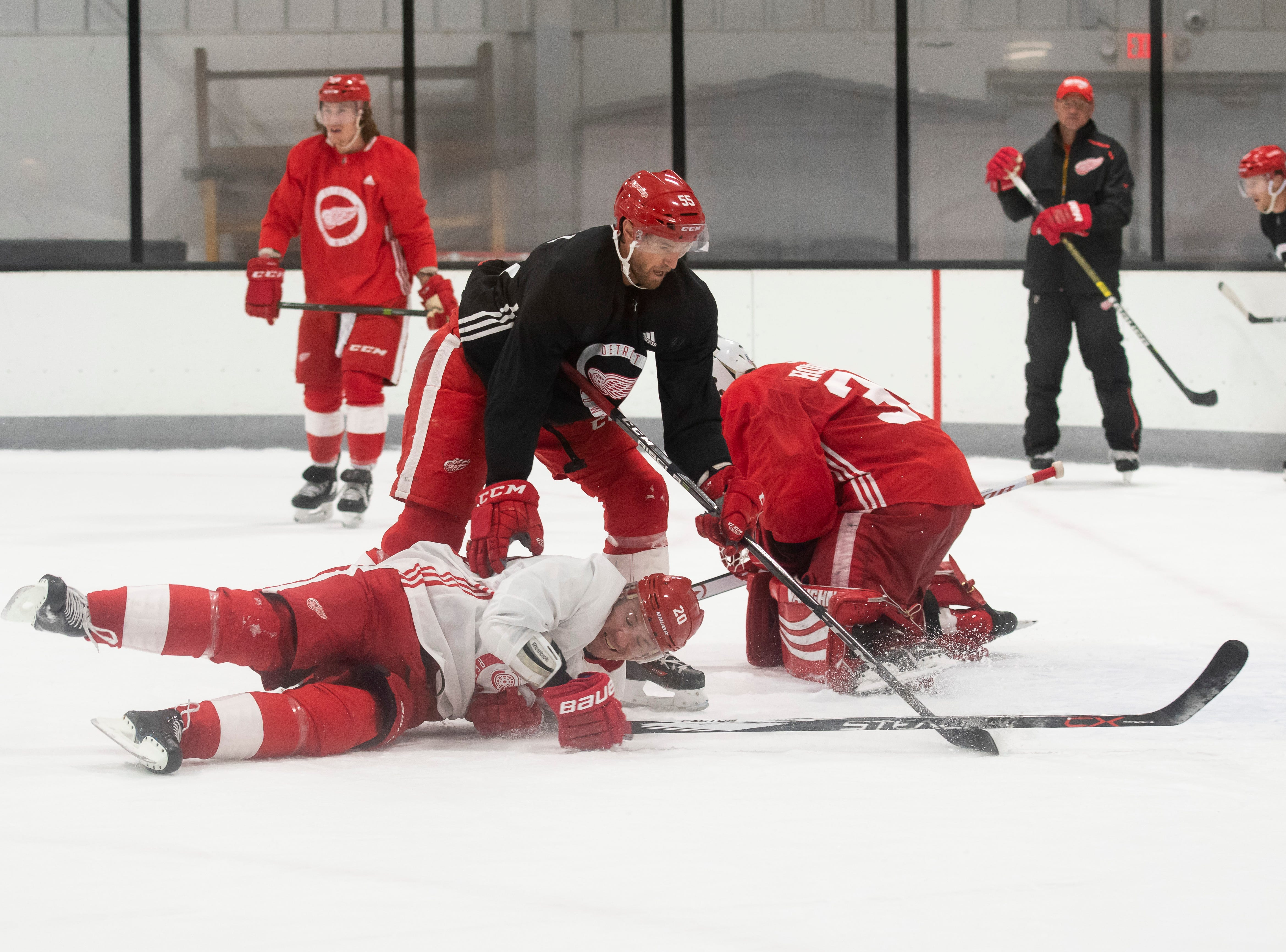 Detroit forward Jussi Jokinen crashes to the ice as he battles for the puck with Detroit defenseman Niklas Kronwall in front of Detroit goaltender Jimmy Howard during practice.