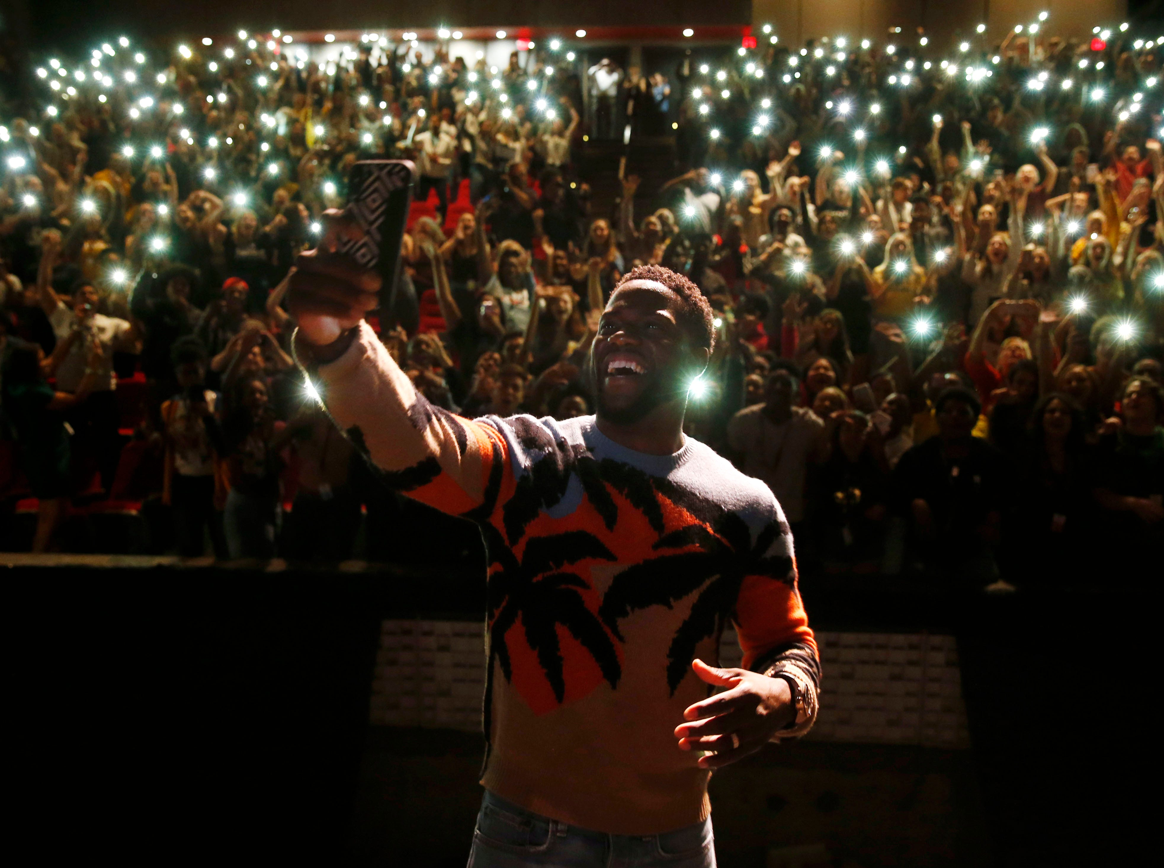 In this Sept. 12, 2018 photo, comedian and actor Kevin Hart films himself with a cellphone after talking to the students at Booker T. Washington High School in Dallas. Hart was named principal for the day. Hart was in town promoting his new movie, Night School.