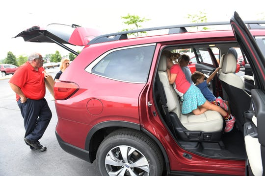 From left, Subaru outfitter Tom Squillace talks with the parents while the McGeehin siblings, Stella, 7, Oliver, 10, and Alastair, 3, all of Grosse Pointe, check out the 2019 Subaru Ascent at Sellers Subaru in Macomb.