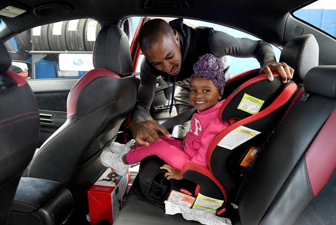 Kyle English, 26, buckles up his daughter, Rylee English, 2, after he gets an oil change for his Subaru WRX STI at Sellers Subaru in Macomb.