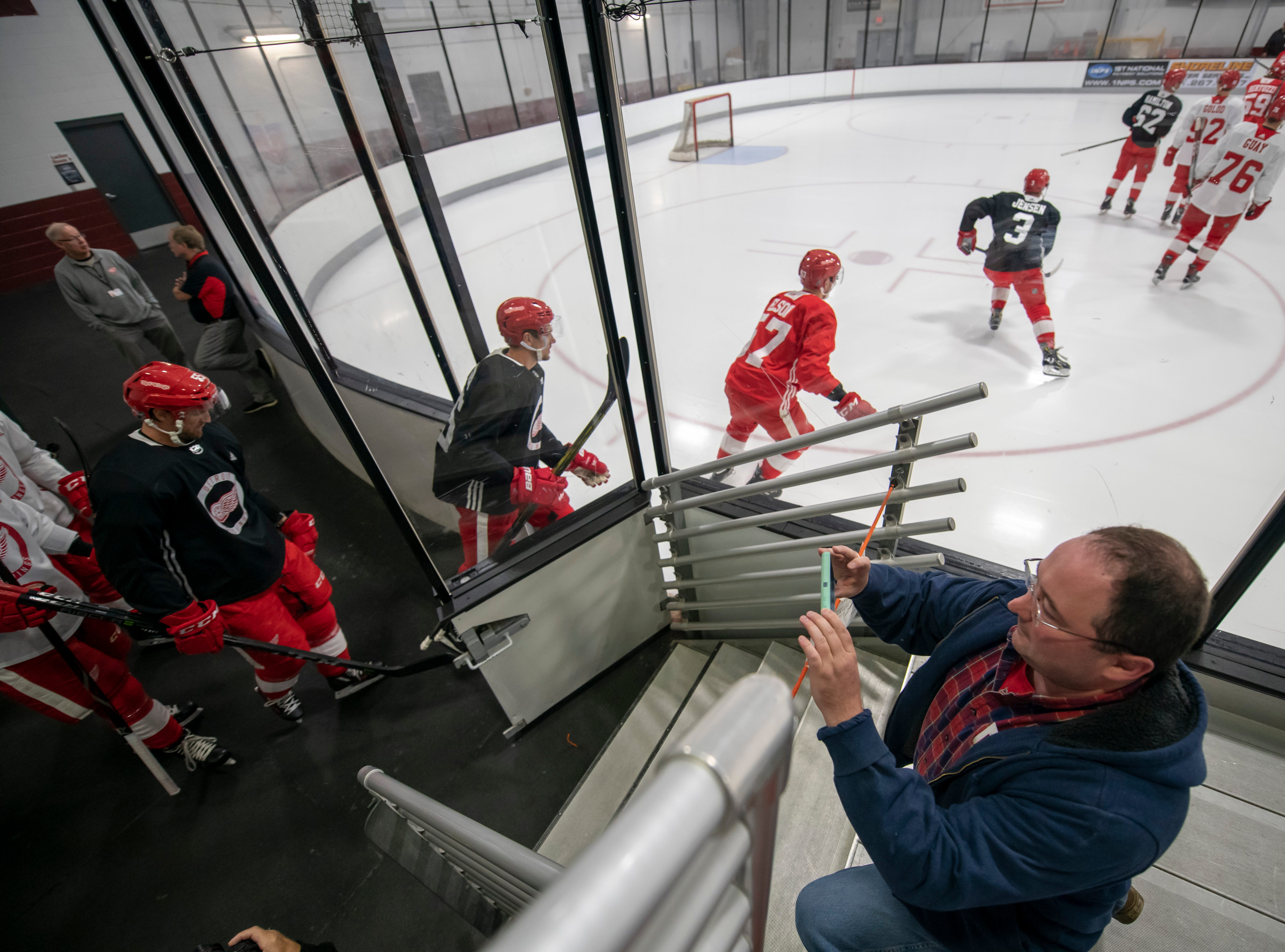 Matthew Best, of Williamston, takes photographs of the Red Wings as they head out onto the ice for the start of camp.            Photos are of the Detroit Red Wings during training camp at Centre Ice Arena, in Traverse City, September 14, 2018.