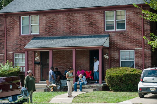 A number of people hangout on the porch in front of an apartment in the 9200 block of Evergreen on Detroit's westside Friday afternoon, September 14, 2018, where earlier in the day a 46-year-old man was shot and killed by police during the execution of a search warrant in connection with the death of a 5-year-old girl late Thursday, according to Detroit police. Irate family members of the unidentified man said at the scene he had nothing to do with the girl's death and say police were doing a search of the home at 4:50 a.m. in a scene that jolted the neighborhood.