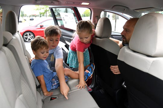 From left, Alastair McGeehin, 3, Oliver McGeehin, 10, and Stella McGeehin, 7, check out the middle seat of a 2019 Subaru Ascent with dad Ross McGeehin, all of Grosse Pointe, at Sellers Subaru in Macomb.