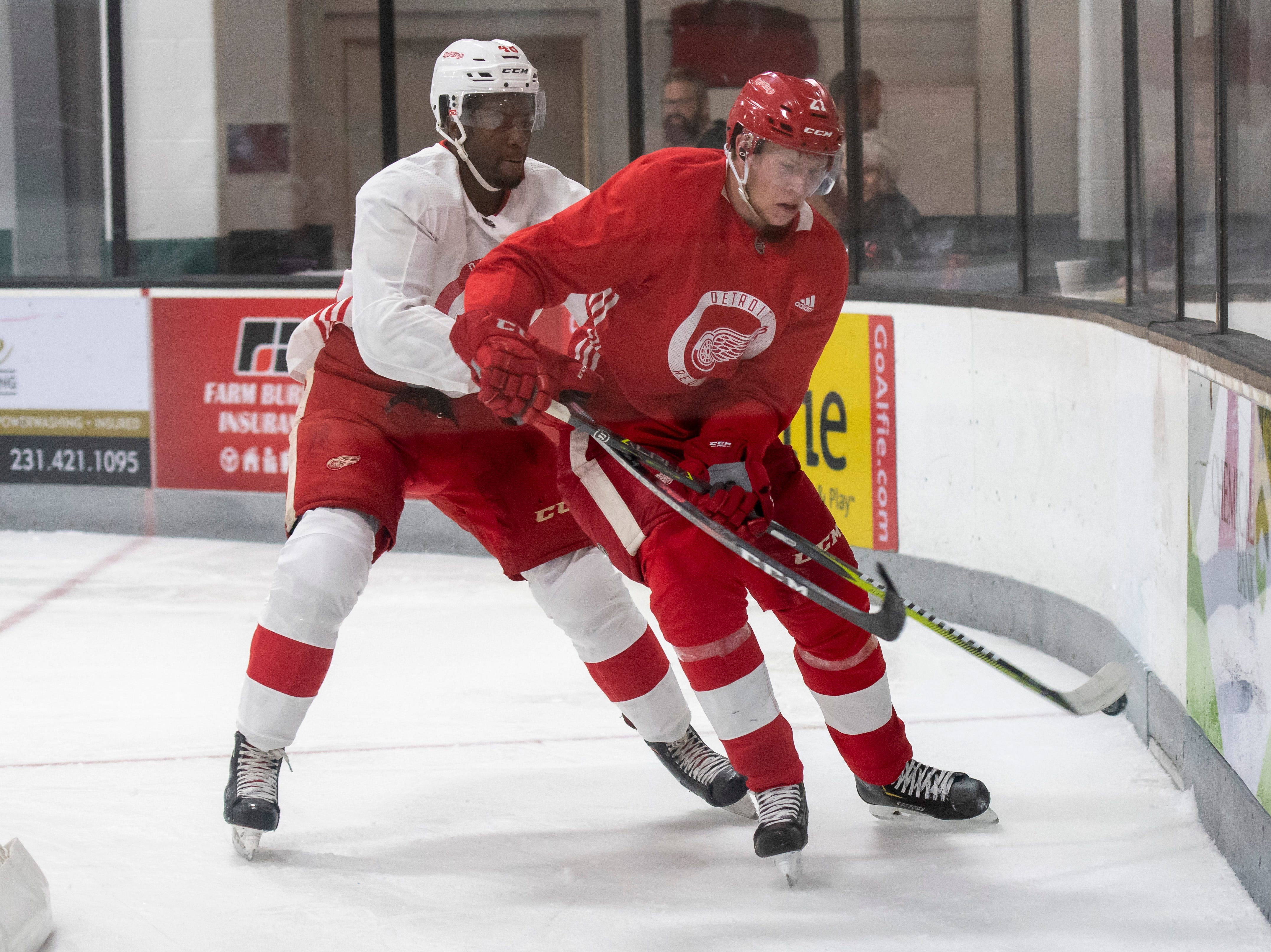 Detroit forward Givani Smith, left, and defenseman Dennis Cholowski battle for the puck during a scrimmage.