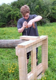 Eagle Scout Andrew Joiner of Pine City drills a nesting platform for an osprey nesting pole.