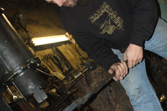 Mike Deibert uses a power hammer to expand a blade at his Alabama home.