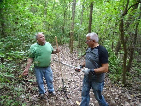 Terra State Community College employees Jerry Buccilla, right, and John Carpenter help clear brush along one of Camp Fire Sandusky County's trails Friday as part of the college's Community Service Day