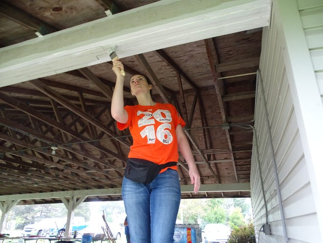 Terra State Community College employee Amy Reeves paints inside the shelter house at Camp Fire Sandusky County Friday as part of the college's Community Service Day.
