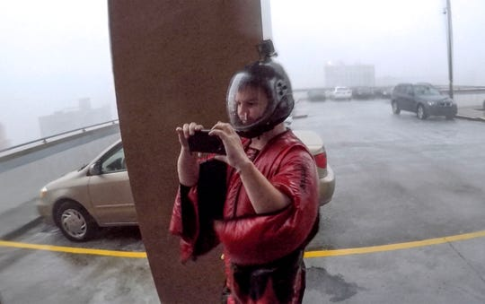 Michael Henderson of Tennessee, a professional skydiver, stands on the seventh floor of a parking garage in downtown Wilmington, North Carolina, as Hurricane Florence just hit land on Friday, September 14, 2018. Henderson said he always wanted to try out his wing suit during a hurricane. (Ken Ruinard / Greenville News / Gannett USA Today Network / 2018 )