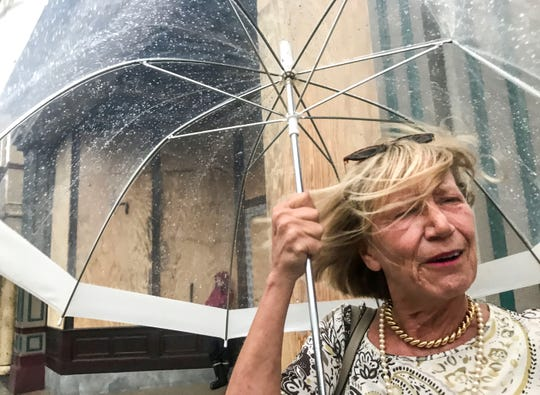 Karen Day of Wilmington bears with rain and wind walking to the Slainte Irish Pub in downtown Wilmington, North Carolina on Thursday, September 13, 2018.  Day said her power was out and decided to join others at one of the few businesses open in downtown. (Ken Ruinard / Greenville News / Gannett USA Today Network / 2018 )