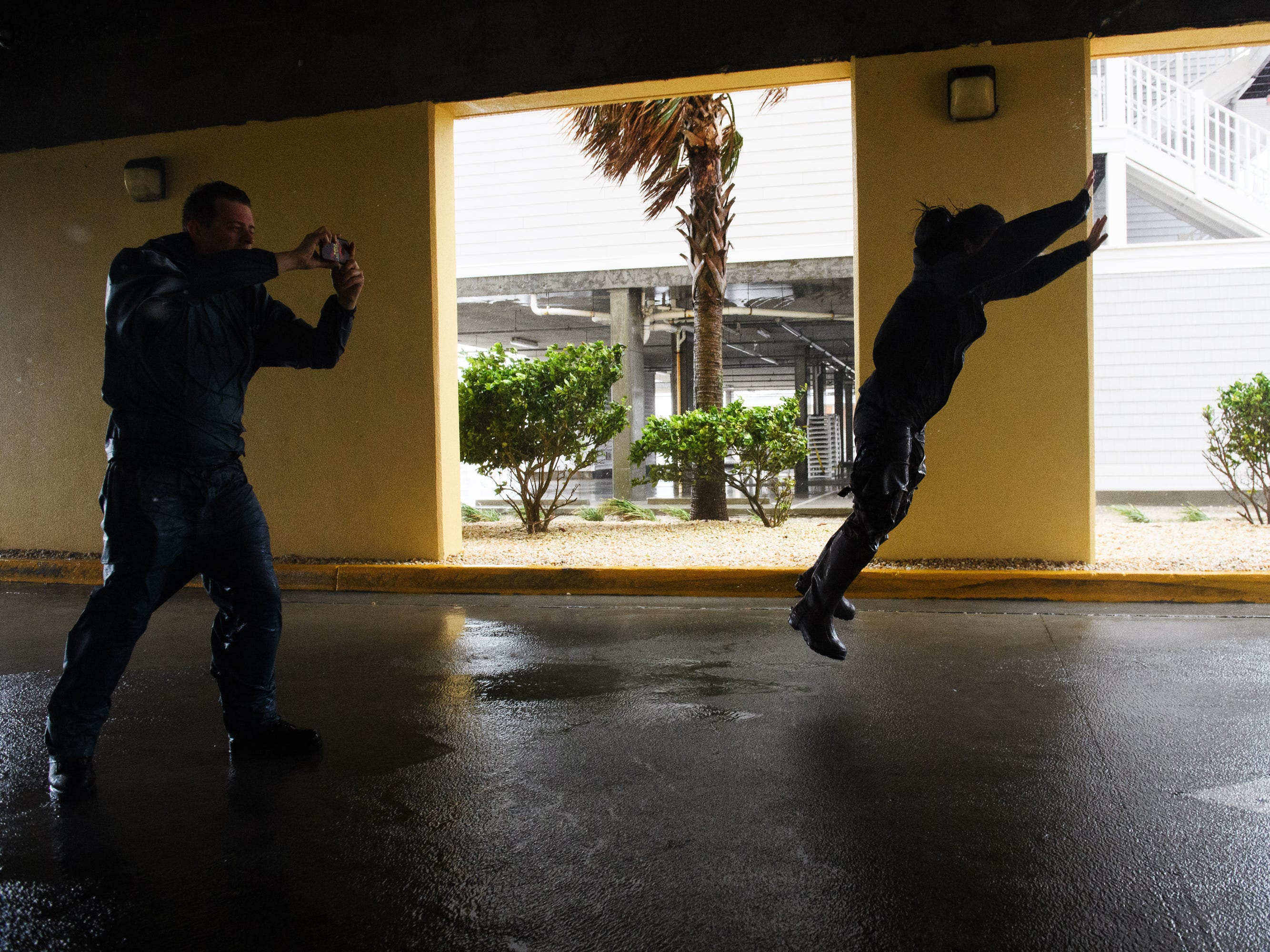 Storm chasers Brandon Jarvis, left, and Emily Pike try to suspend themselves in the air in a wind tunnel at a parking garage in North Myrtle Beach as wind speeds begin to increase due to Hurricane Florence on Friday, Sept. 14, 2018.