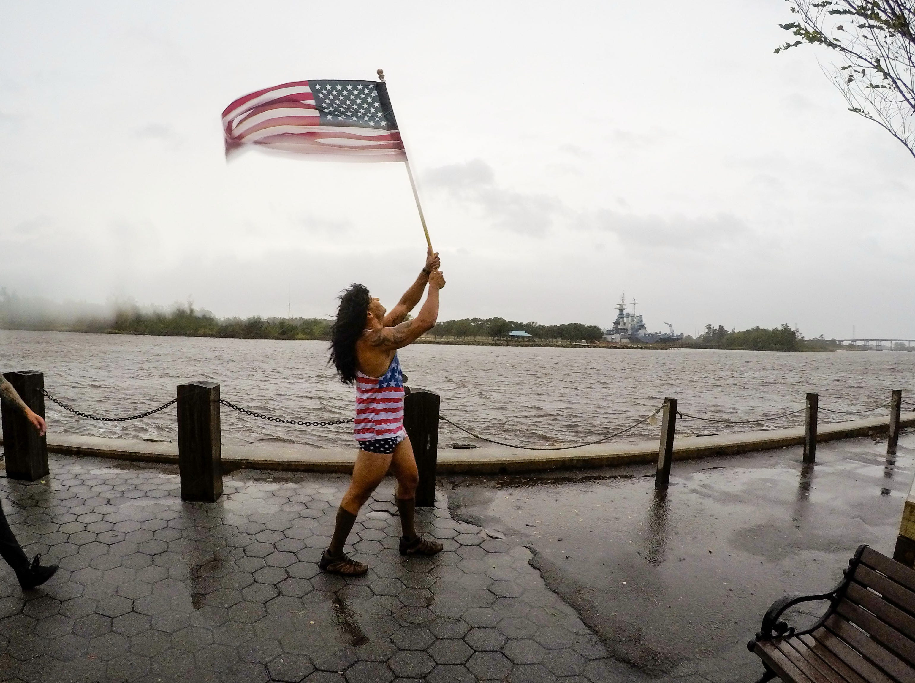 Jeff Egyp carries a United States flag in windy conditions along the Cape Fear River in downtown Wilmington, North Carolina on Thursday, September 13, 2018. (Ken Ruinard / Greenville News / Gannett USA Today Network / 2018 )