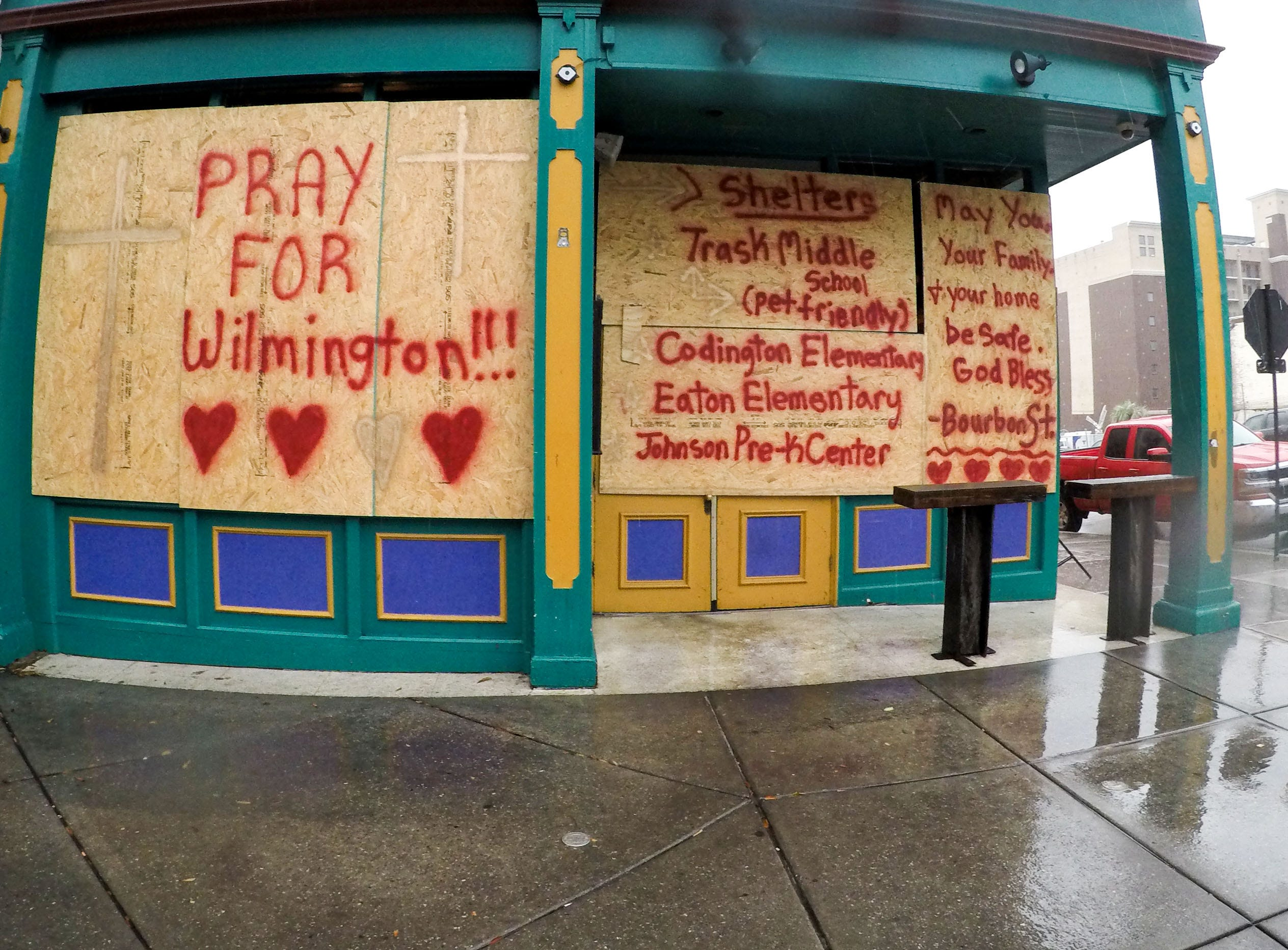 A woman stands near a business with plywood with Pray for Wilmington and a list of shelters, in downtown Wilmington, North Carolina on Thursday, September 13, 2018. (Ken Ruinard / Greenville News / Gannett USA Today Network / 2018 )