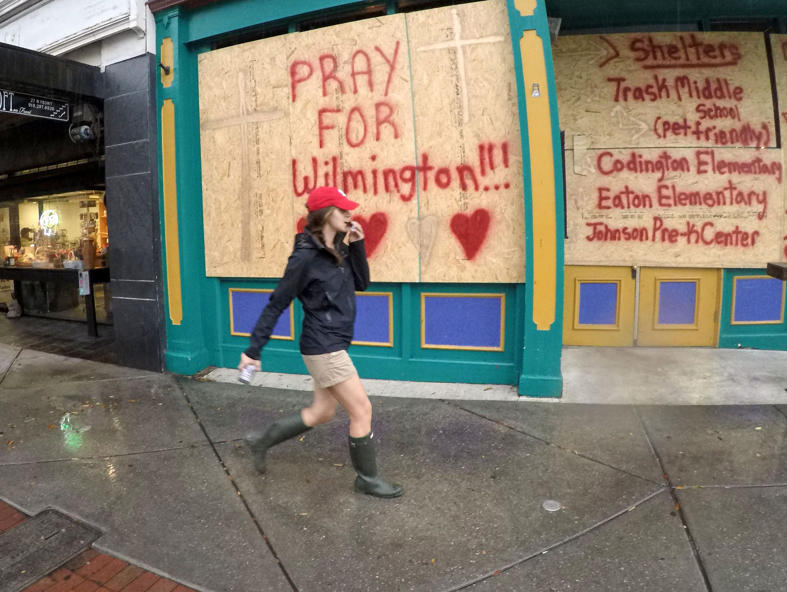 A woman walks by a business with plywood with Pray for Wilmington and a list of shelters, in downtown Wilmington, North Carolina on Thursday, September 13, 2018. (Ken Ruinard / Greenville News / Gannett USA Today Network / 2018 )