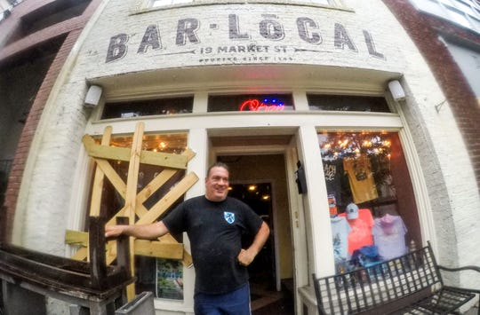 Dennis Mancinelli, owner of Bar Local, stands by his front door with one window boarded up with wood in downtown Wilmington, North Carolina on Thursday, September 13, 2018. (Ken Ruinard / Greenville News / Gannett USA Today Network / 2018 )