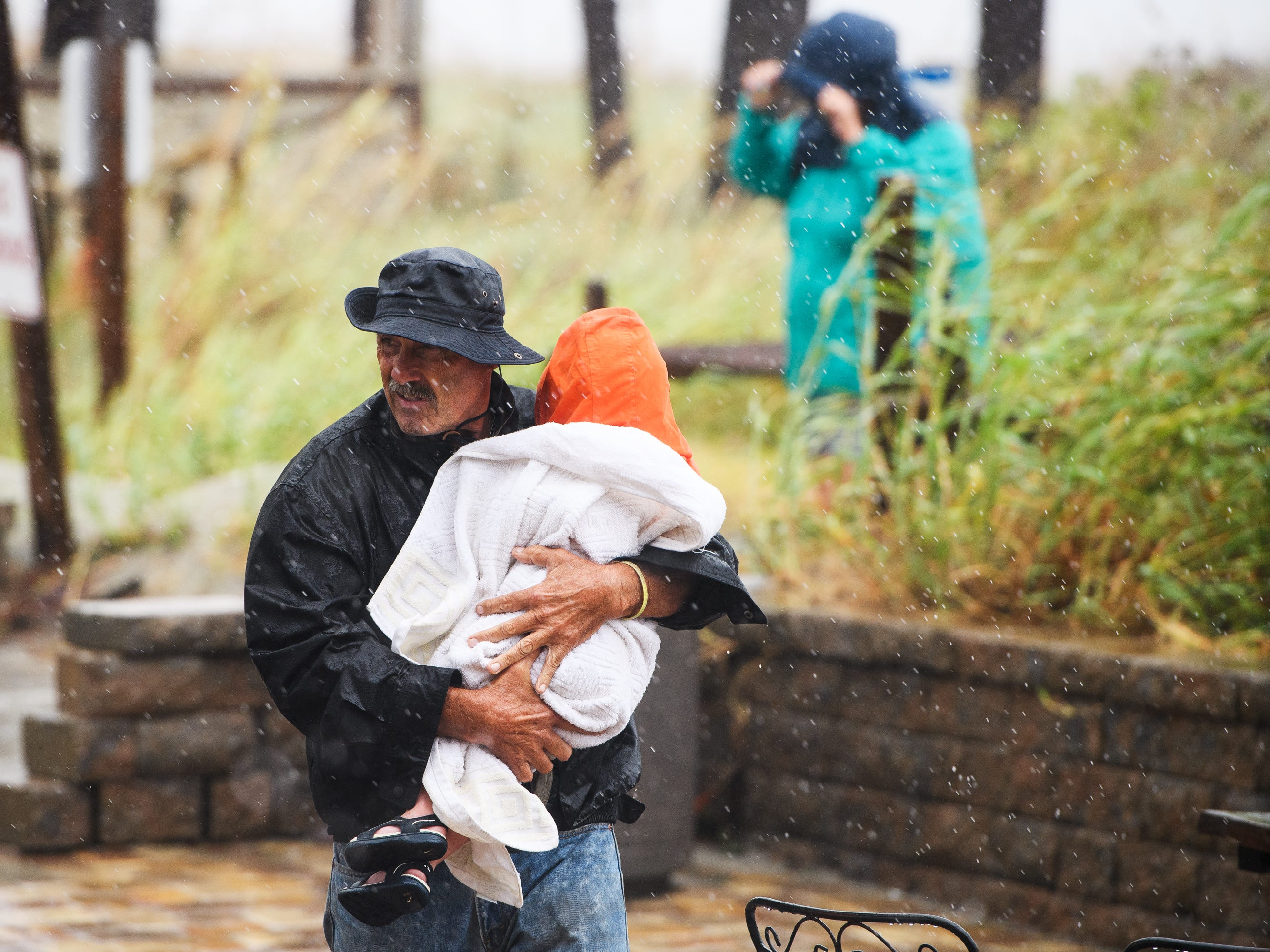 Joe Lewis carries two-year-old Piper Collins into a covered patio after checking out how Hurricane Florence conditions have affected the beach in North Myrtle Beach on Friday, Sept. 14, 2018.