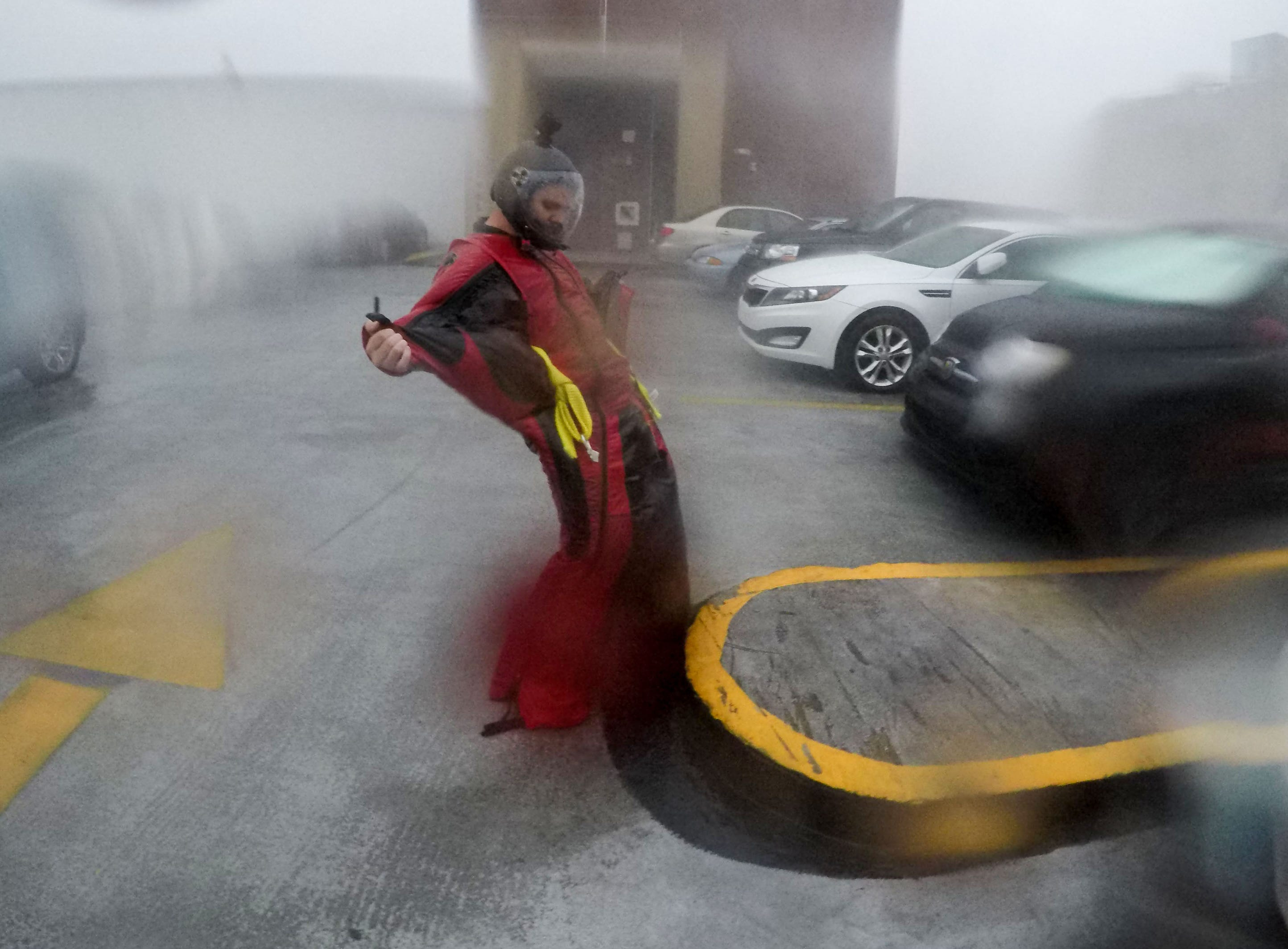 Michael Henderson of Tennessee, a professional skydiver, stands on the seventh floor of a parking garage in downtown Wilmington, North Carolina, as Hurricane Florence just hit land on Friday, September 14, 2018. Henderson was testing out his wing suit in hurricane conditions.  (Ken Ruinard / Greenville News / Gannett USA Today Network / 2018 )