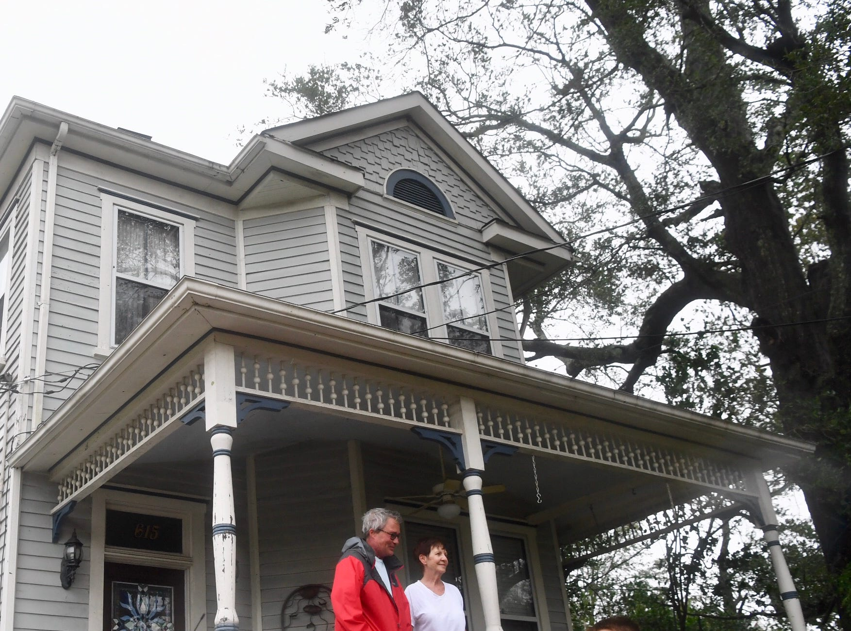 Jeff and Mary Holland stand on the porch of their 1889 home they bought 5 years ago as Hurricane Florence passes through Friday, Sept. 14, 2018, in Wilmington NC. The roof they replaced after Hurricane Matthew damaged it years ago was unscathed.