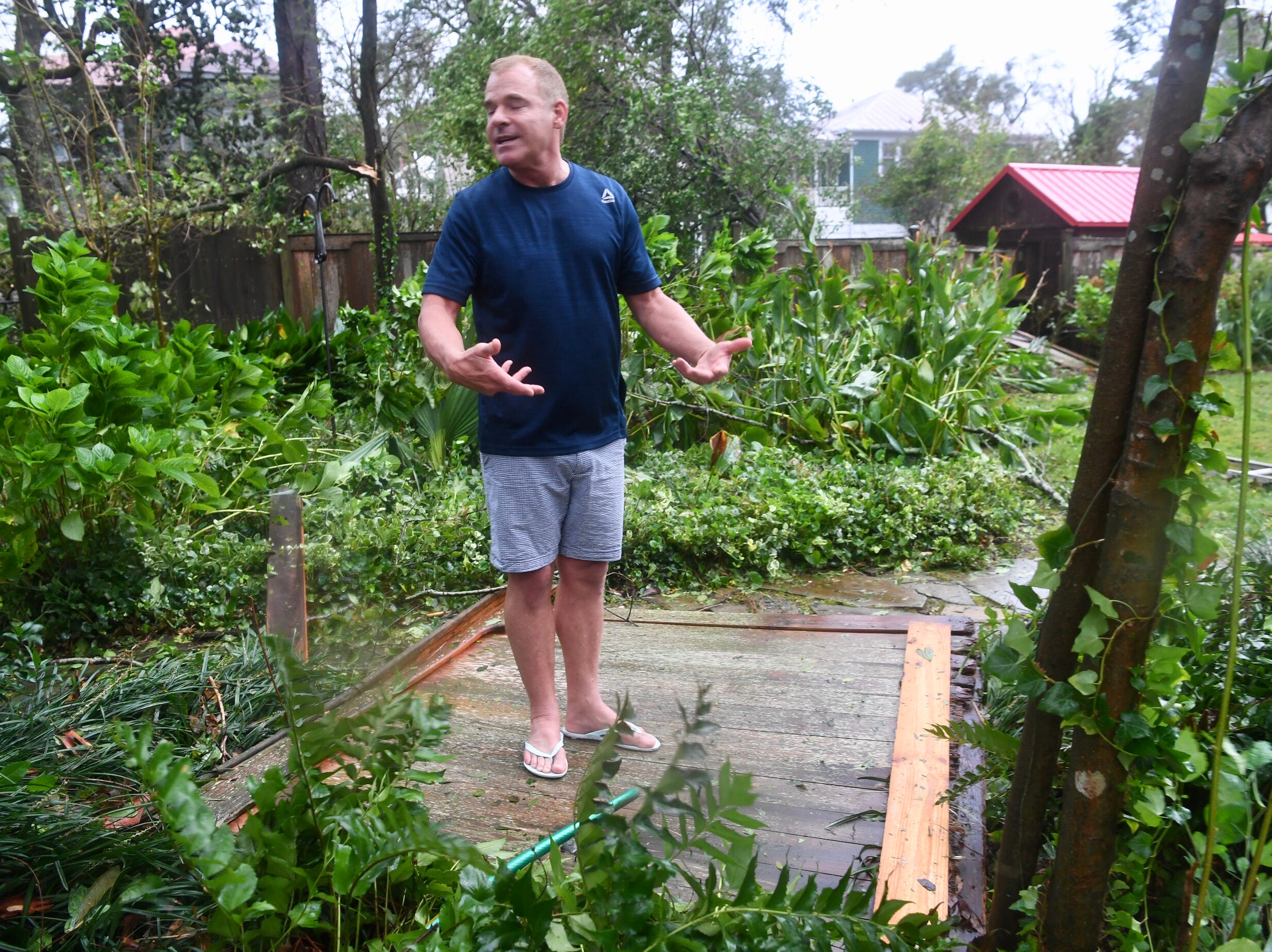 Charles Carver stands on a part of his fence blown down in his Wilmington NC home as Hurricane Florence continues to blow through his historic neighborhood on Friday, Sept. 14, 2018.