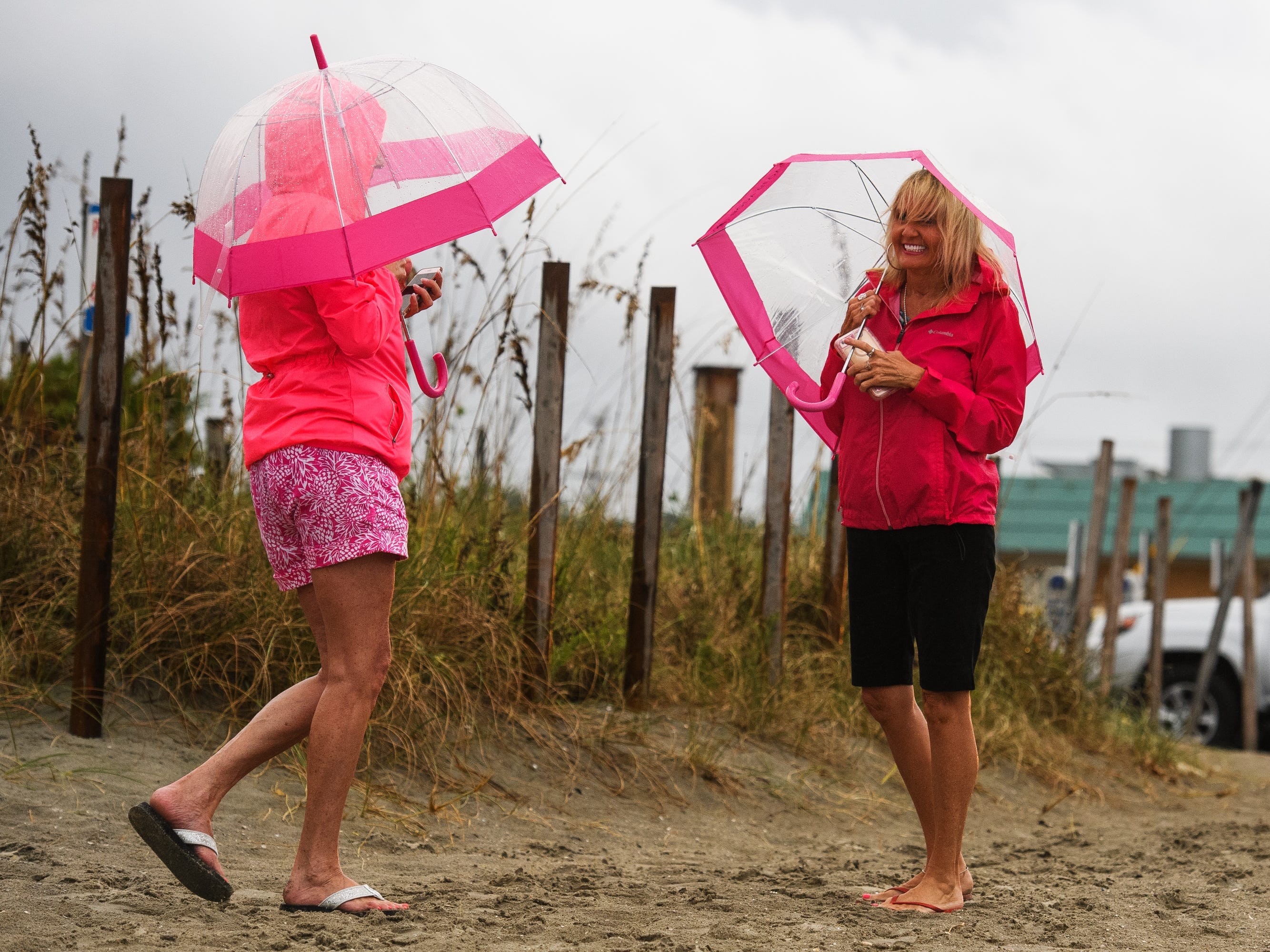 Karen Glass, left, and Deborah Murray leave Cherry Grove Beach in North Myrtle Beach after being informed of a curfew due to the arrival of Hurricane Florence on Thursday, Sept. 13, 2018.