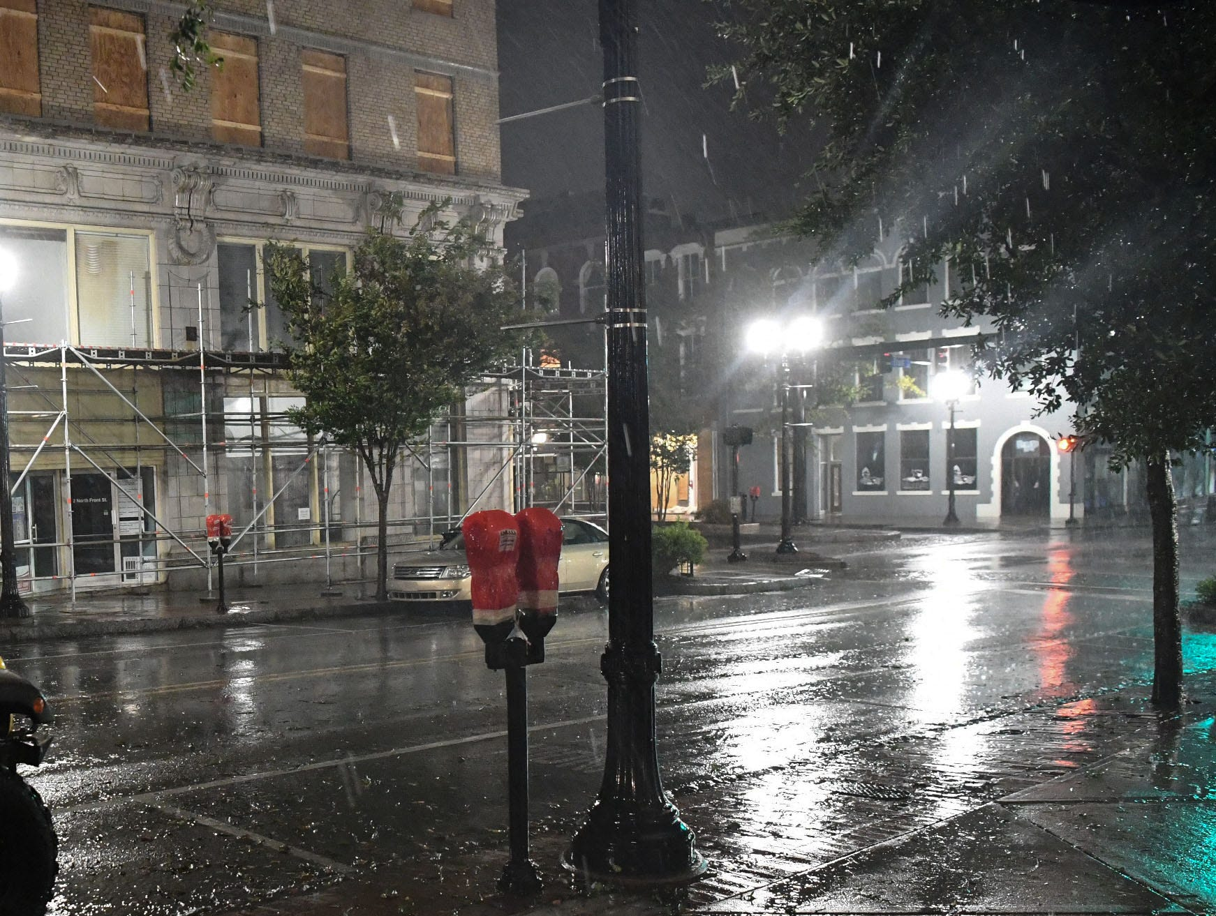 Windows and a parking meter is are covered while wind and rain gust early in the morning in downtown Wilmington, North Carolina on Friday, September 14, 2018. (Ken Ruinard / Greenville News / Gannett USA Today Network / 2018 )
